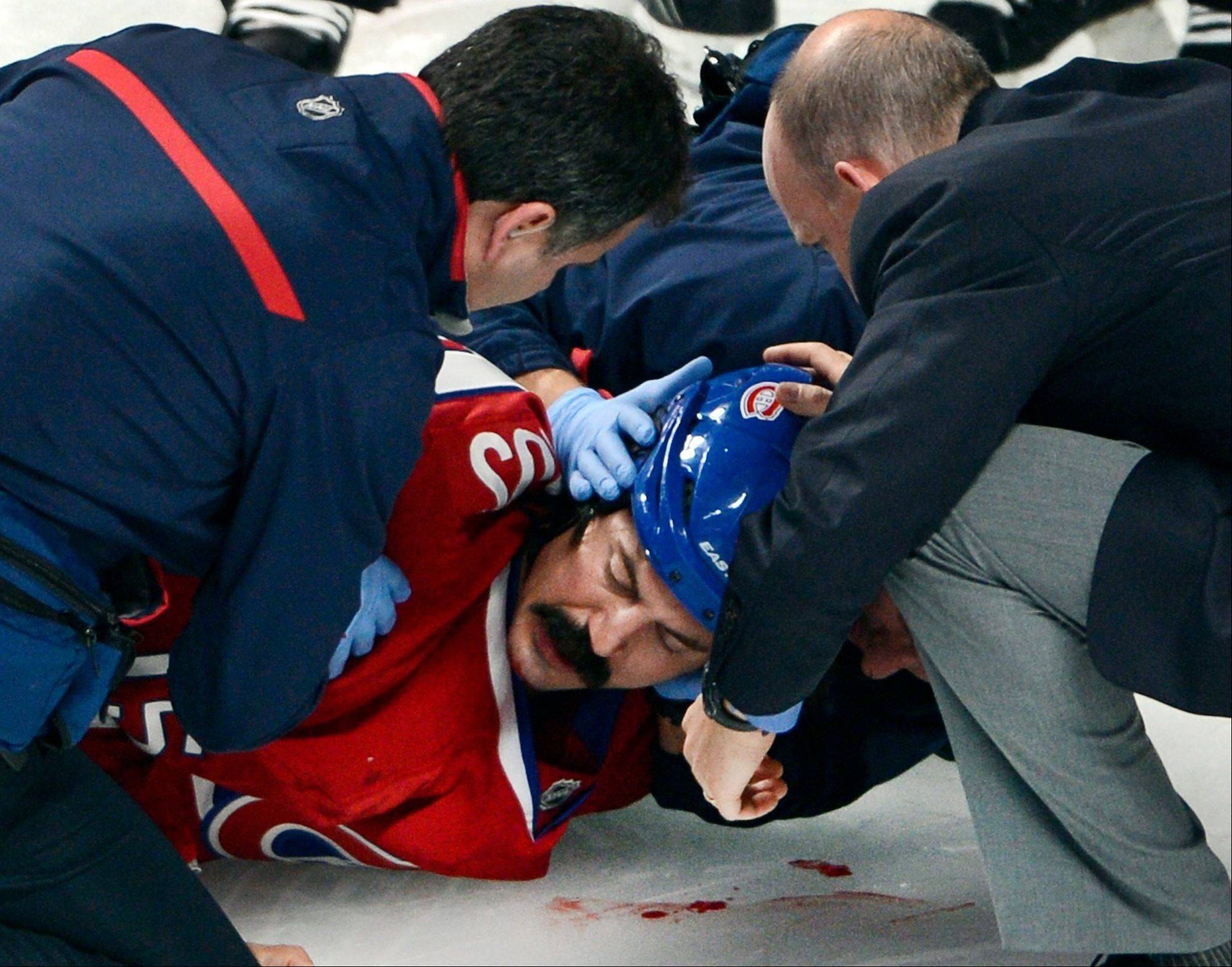 Montreal Canadiens winger George Parros (15) is treated Tuesday by medical staff after he hit his head on the ice during a fight with Toronto Maple Leafs right wing Colton Orr during third period NHL action in Montreal. Parros sustained a concussion.