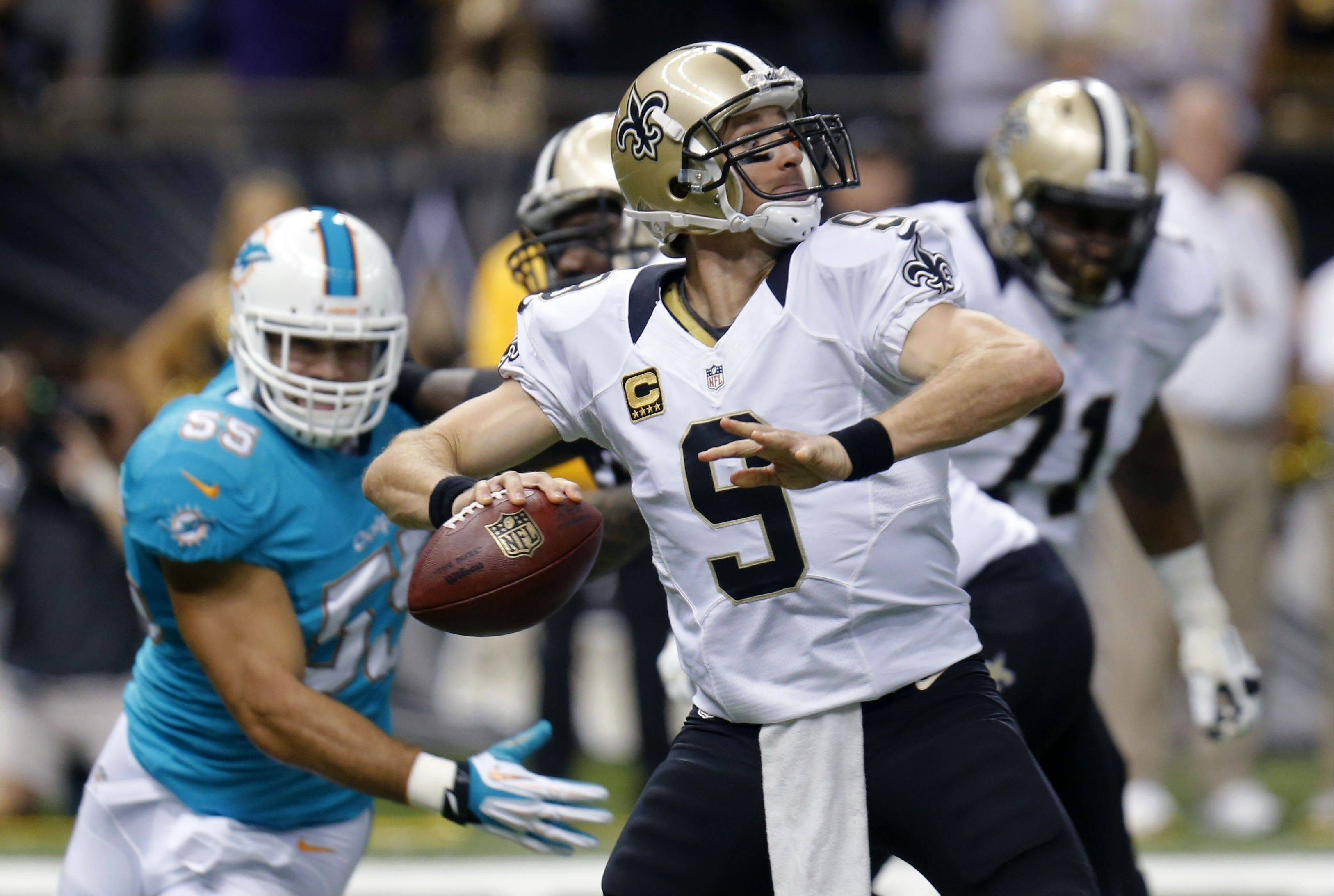 New Orleans Saints quarterback Drew Brees passes as Miami Dolphins outside linebacker Koa Misi rushes in the first half in New Orleans.