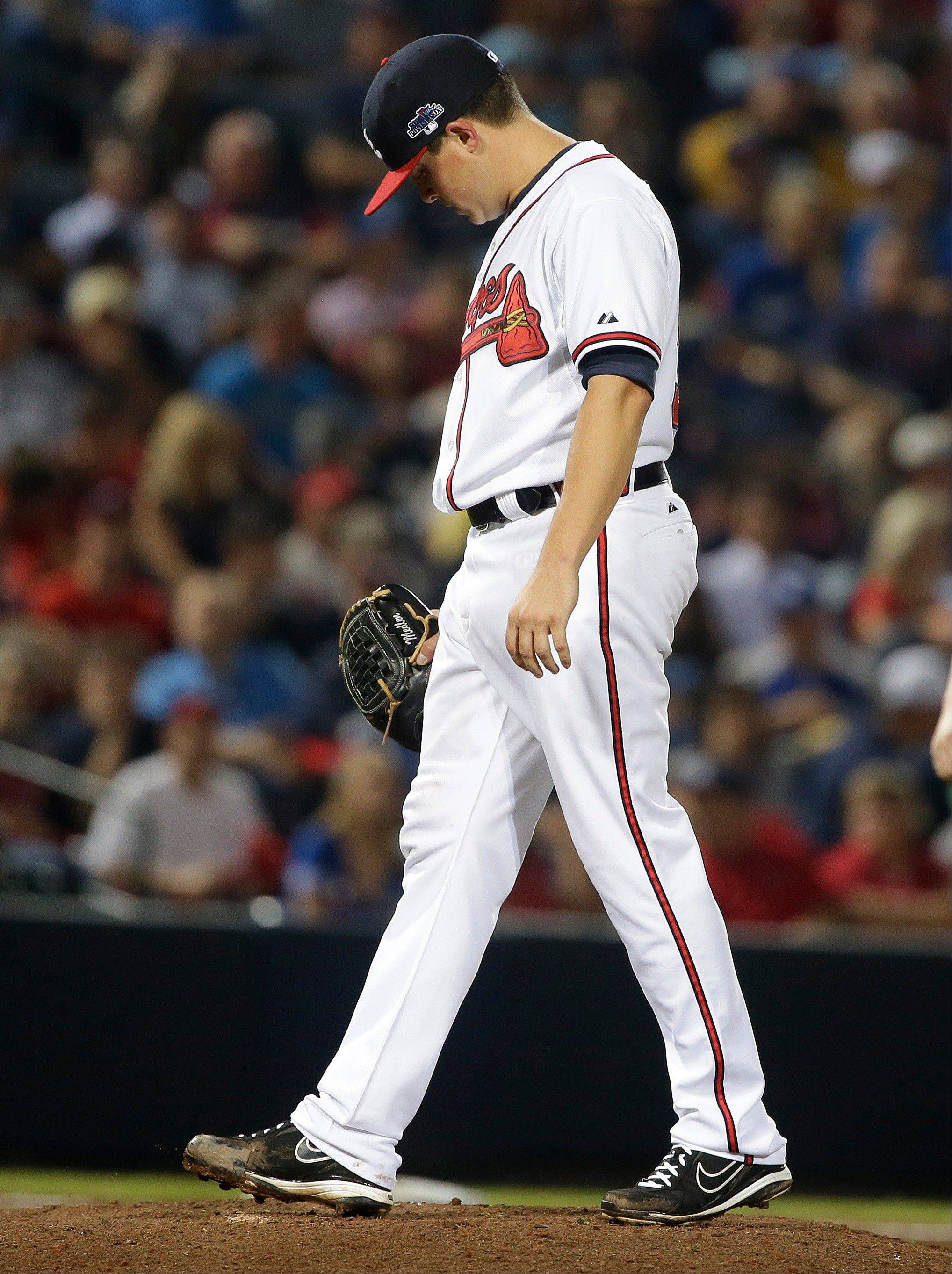 Atlanta Braves starting pitcher Kris Medlen walks to Atlanta Braves manager Fredi Gonzalez as he is relieved in the fifth inning of Game 1 of the National League Division Series against the Los Angeles Dodgers, Thursday, Oct. 3, 2013, in Atlanta.
