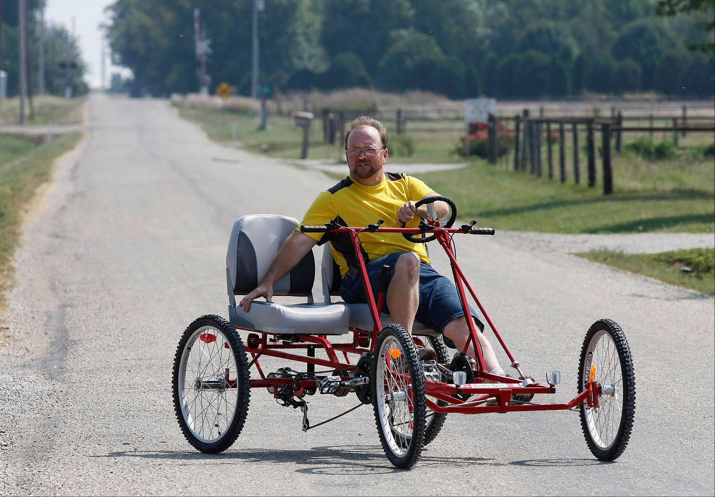 Sales representative Rich Flavin demonstrates a ride in the Quadra Sport Quadracycle, a unique four-wheel bicycle manufactured in rural Tuscola.