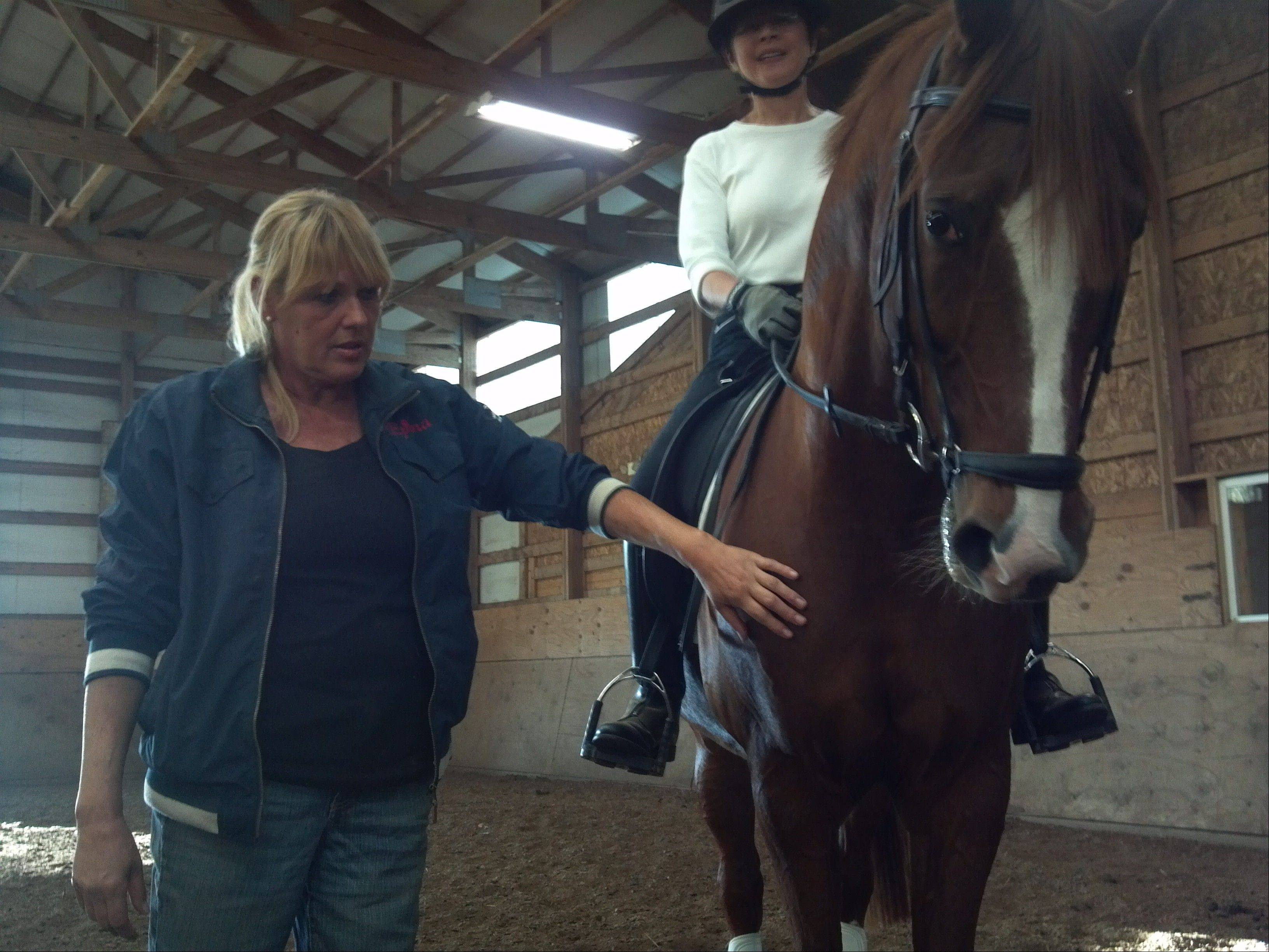 Dora Christensen, left, operator of Epona Farm in Maple Park, sued her neighbor, claiming his motocross track is spooking her horses and ruining her business.