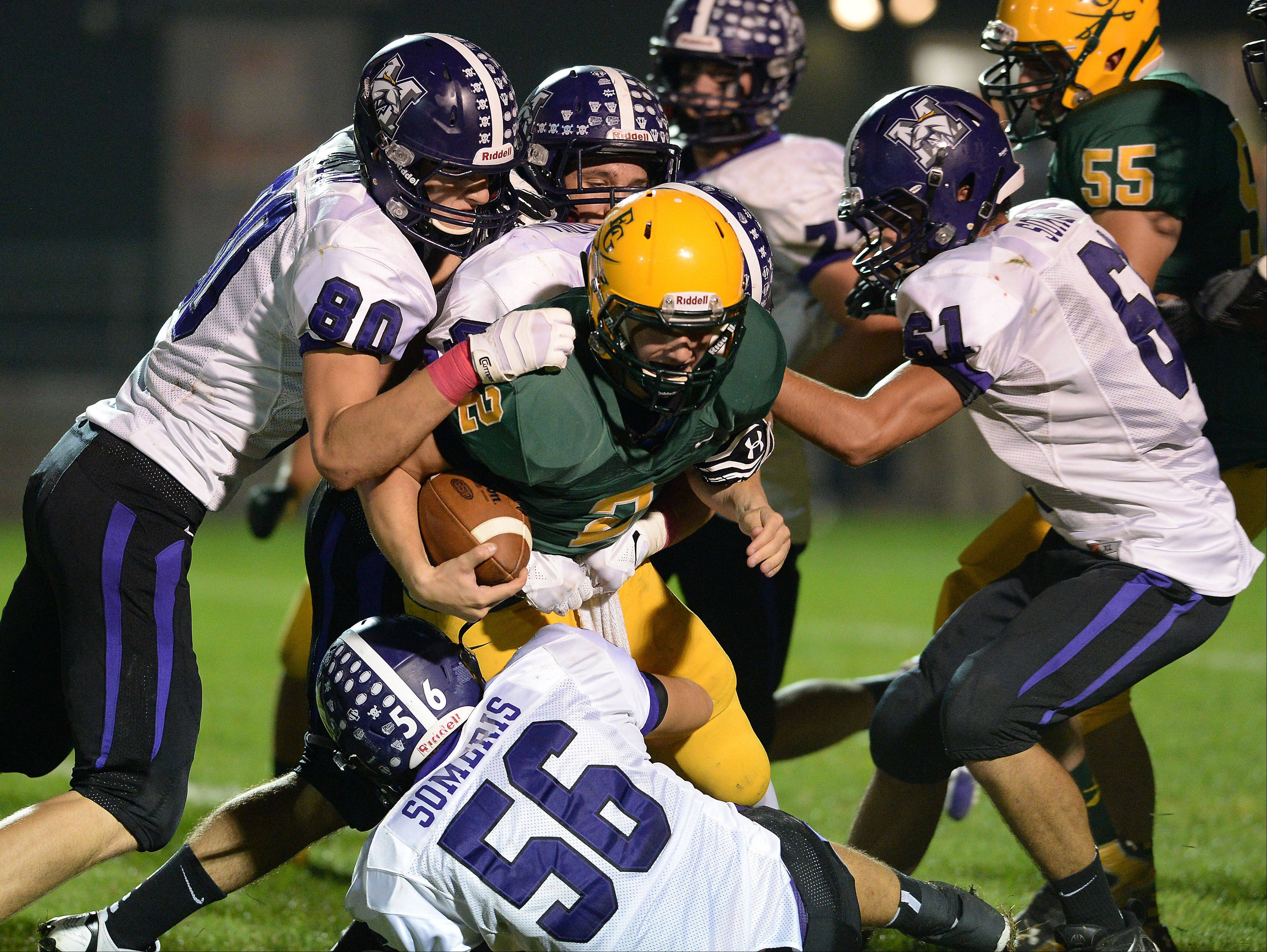 Elk Grove�s Adam O�Malley succumbs to Rolling Meadows� Matt Dolan and a host of Mustangs defenders in the second quarter Friday at Elk Grove.