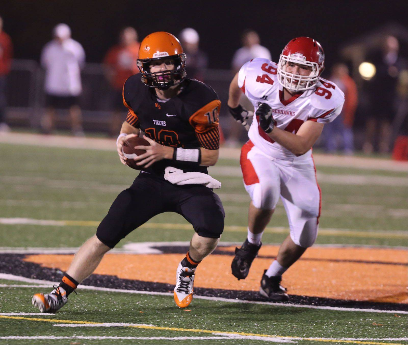Wheaton Warrenville South quarterback Ryan Graham eludes Naperville Central�s Louie Giovannetti .