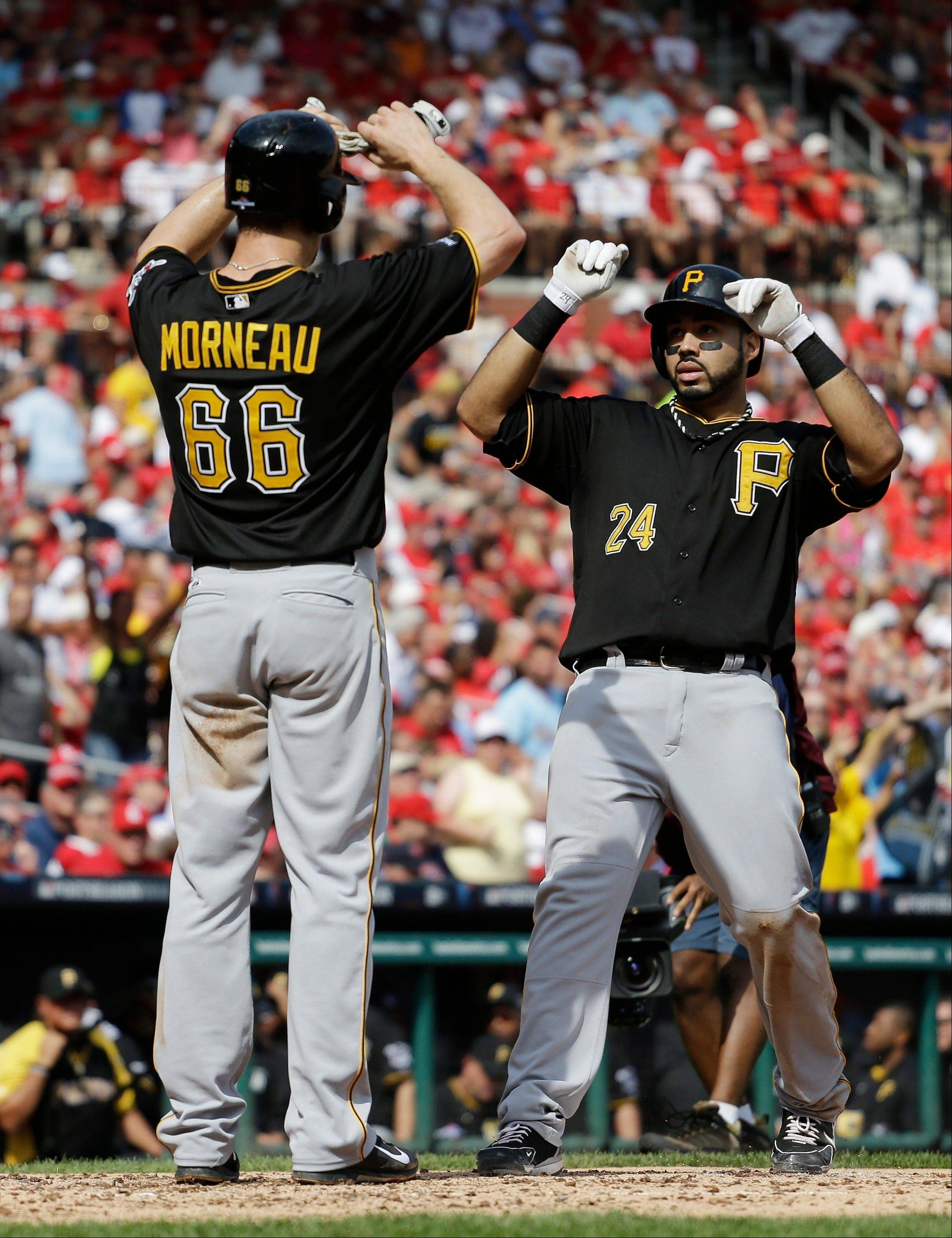 Pittsburgh�s Pedro Alvarez (24) is greeted by Justin Morneau (66) at home plate after Alvarez hit a two-run home run against the St. Louis Cardinals in the third inning of Game 2 of the National League division series on Friday in St. Louis. Morneau scored on the homer.
