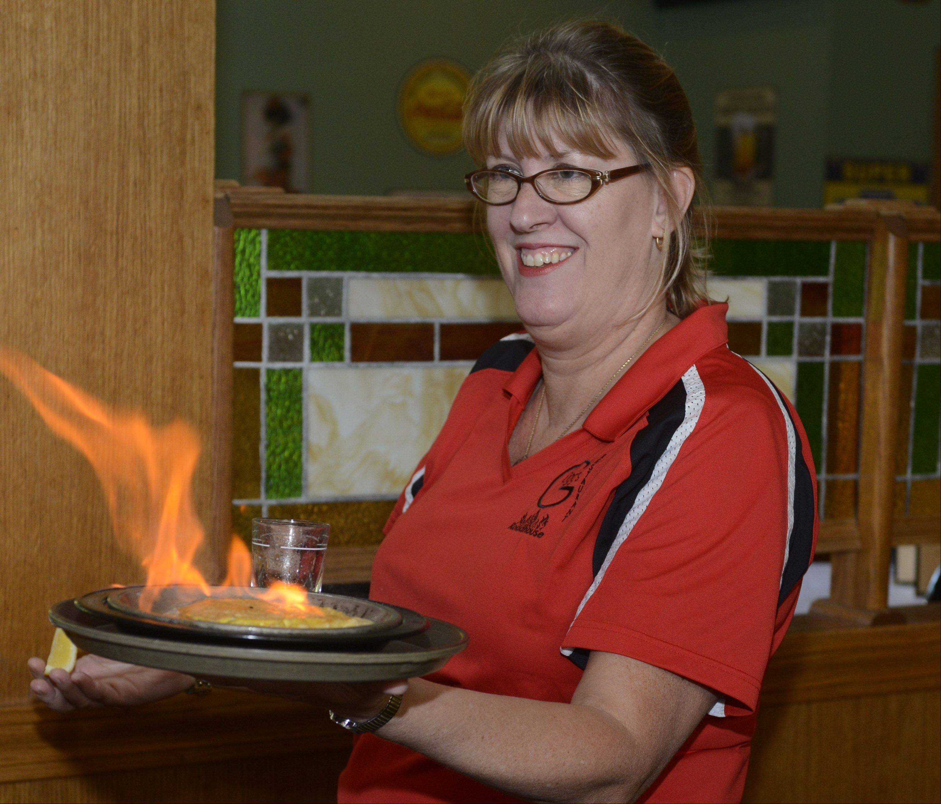 Renee Obey serves an order of saganaki at Gugg's Roadhouse in Vernon Hills.