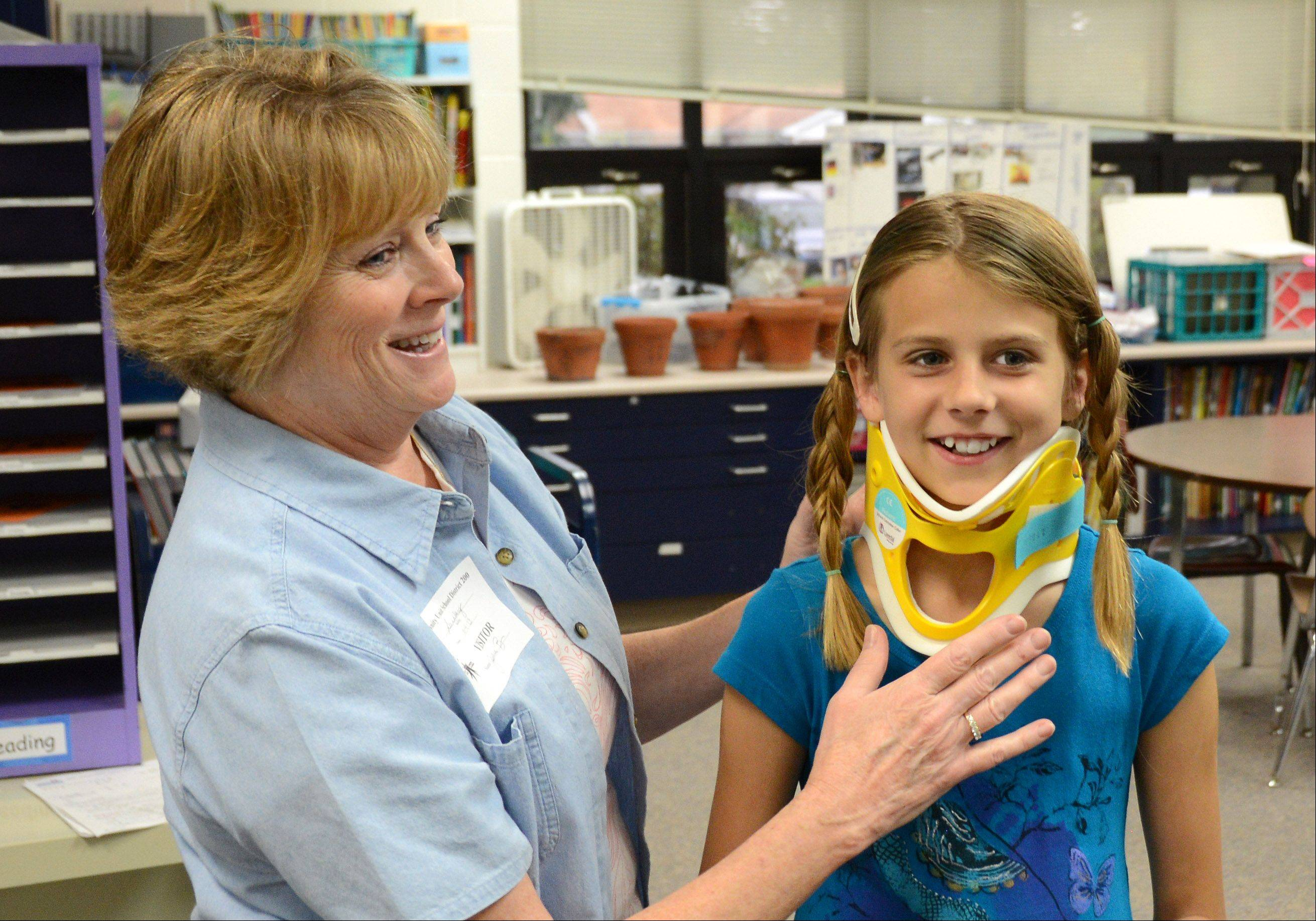 "Fifth-grader Alena Loquorcio tries on a neck brace with the help of Central DuPage Hospital nurse Julie Bernardo. Her uncle wears a similar brace so Alena wanted to ""see how he feels."""