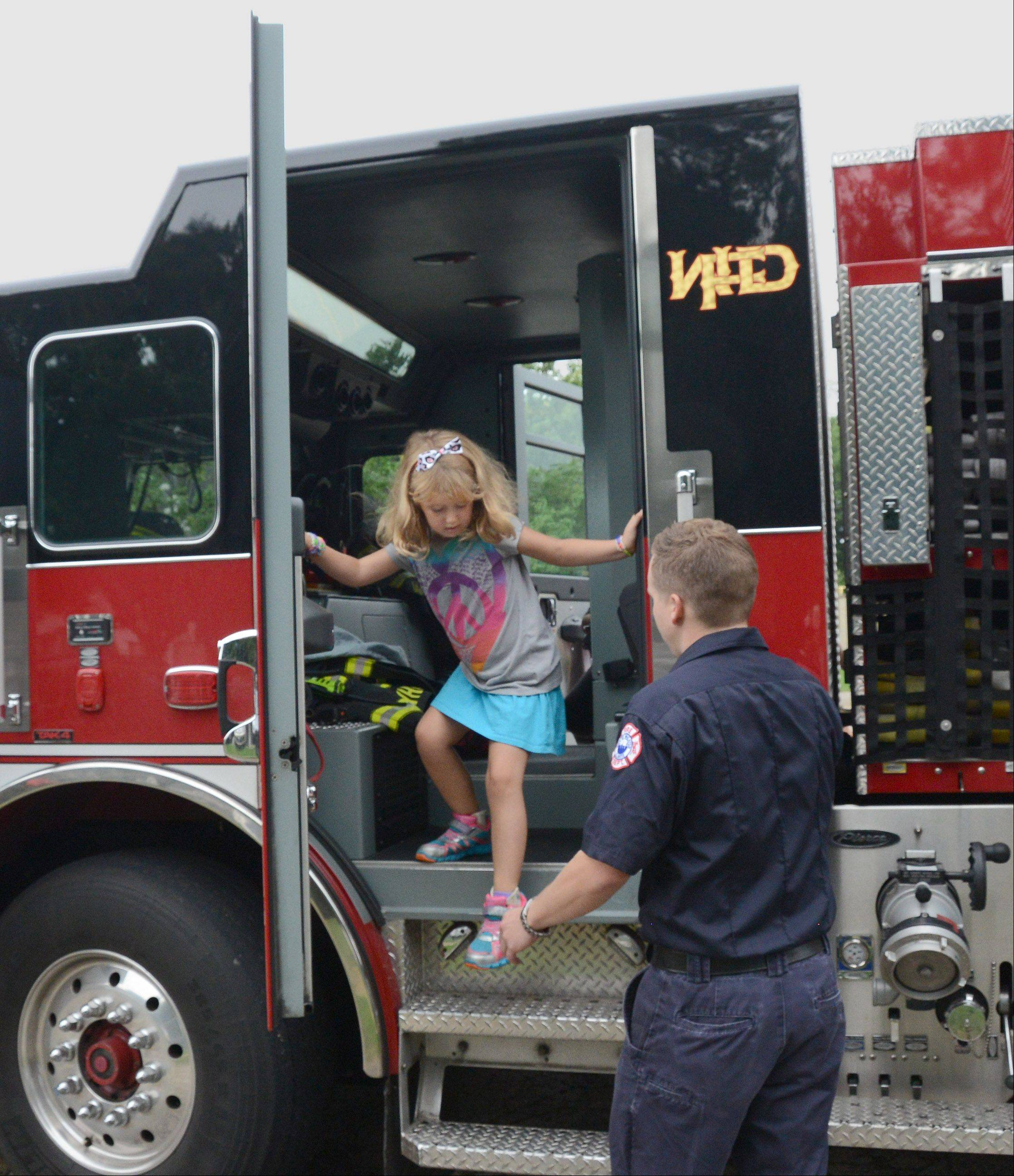 After taking a look around a Wheaton fire engine, Sandburg Elementary School second-grader Madeline White gets a hand climbing down from firefighter Ty Kurth during Friday's Health and Safety Fair at the school.