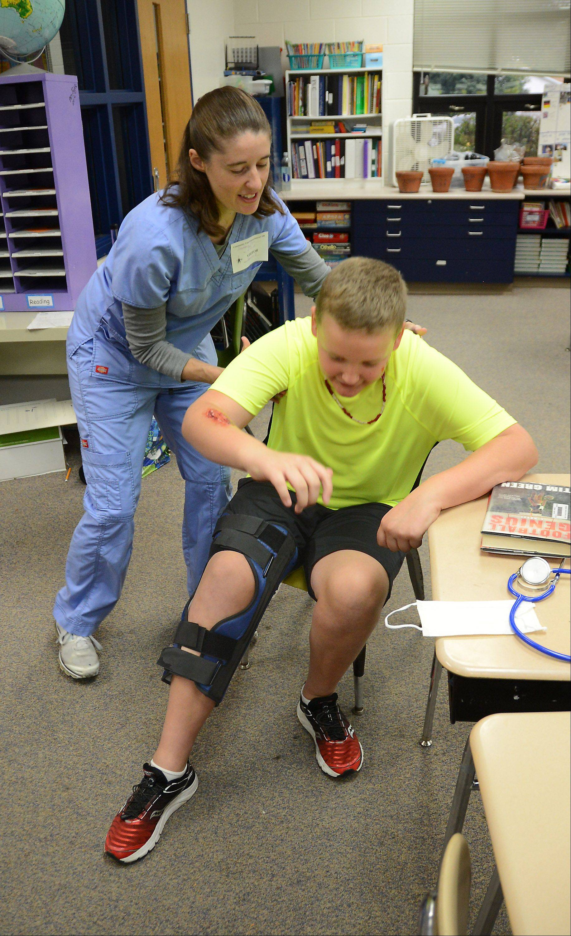 Standing up wasn't as easy as Tyler Crowley expected after being fitted for a leg brace by Central DuPage Hospital nurse Shannon Sprunger during Friday's Health and Safety Fair at Sandburg Elementary School.
