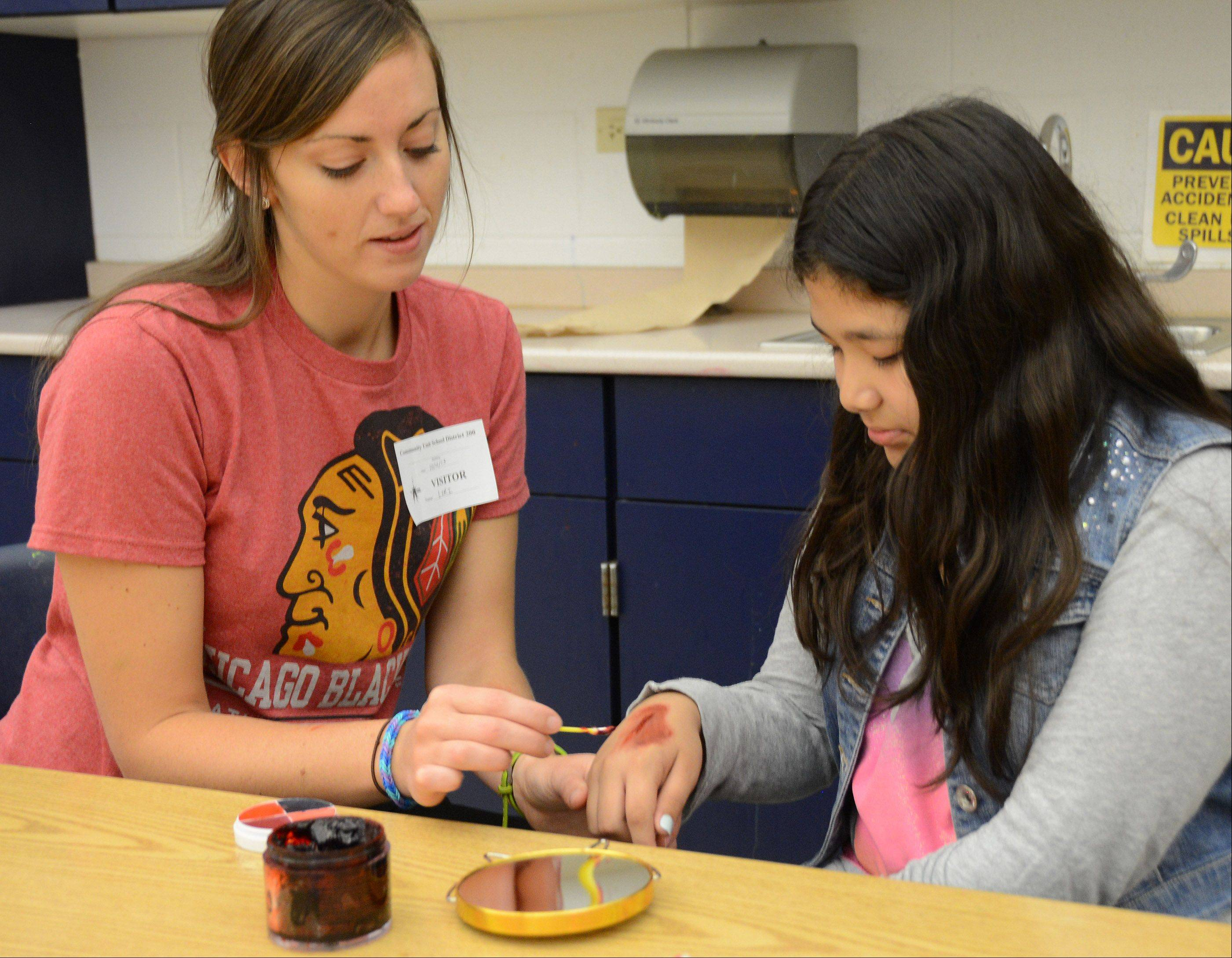 Central DuPage Hospital nurse Lori Bratten, left, fixes up fifth-grader Laura Pineda with a simulated burn.