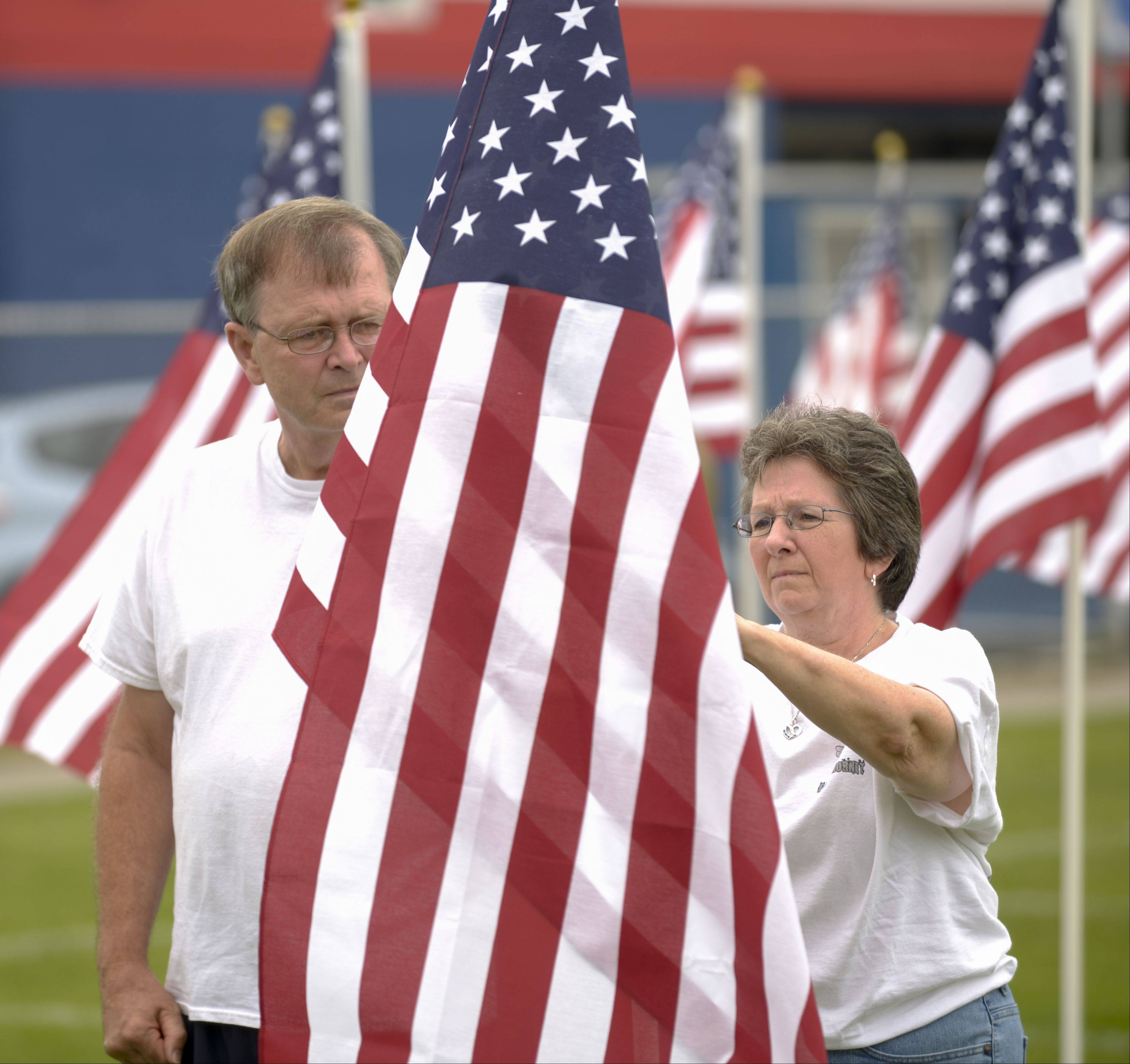 Mike and Mary Kline attach a tag with their son Terrence's name to their flag Friday during a ceremony to preview the Healing Field of Honor at West Aurora High School. Terrence Kline is a Navy pilot on the aircraft carrier George H.W. Bush.