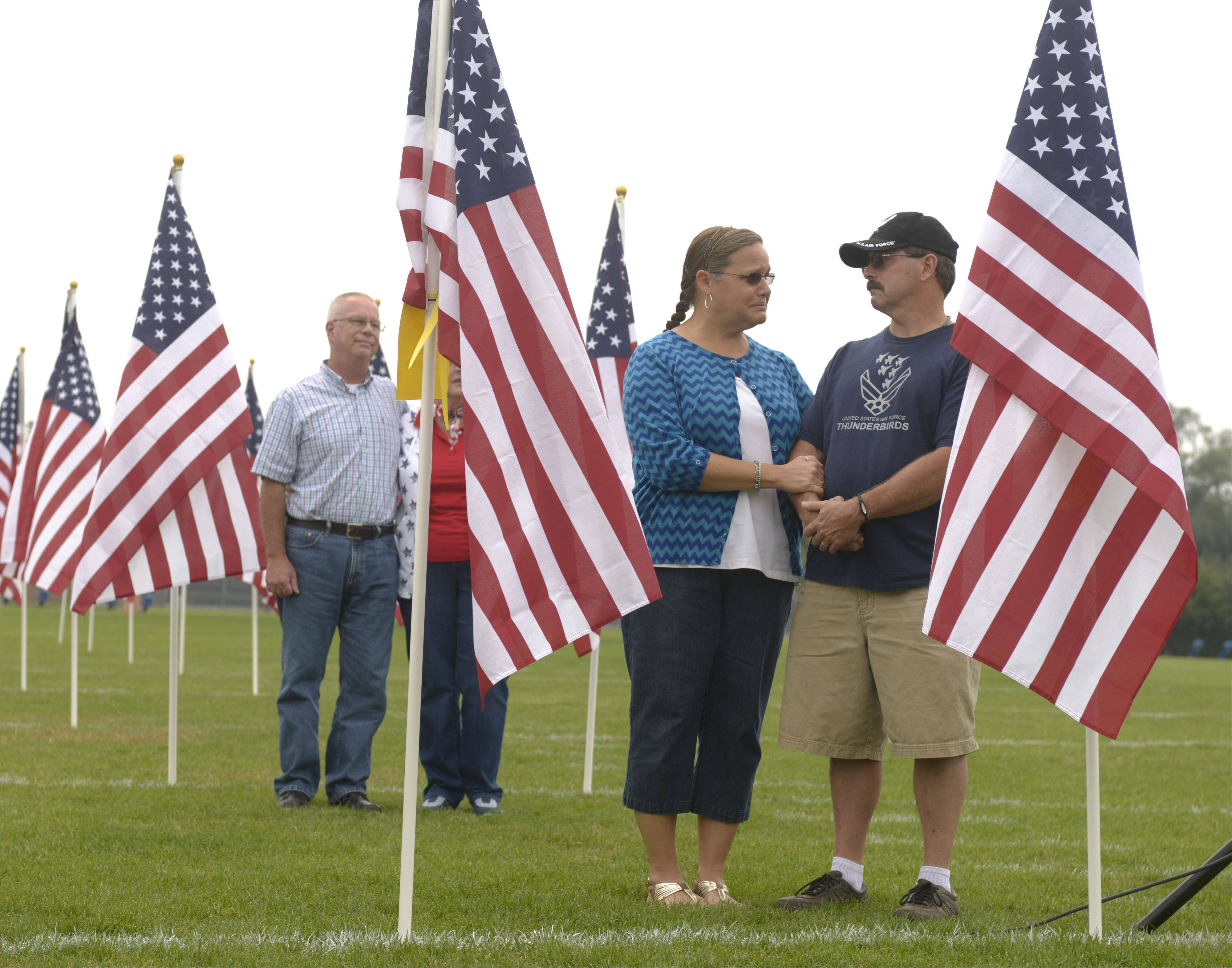 Christine and Bruce Darby of Oswego stand Friday with two flags for their children Nathanial and Allison who both are serving in the Air Force, during a ceremony previewing the Healing Field of Honor at West Aurora High School. The field will be open Nov. 3 to 13.