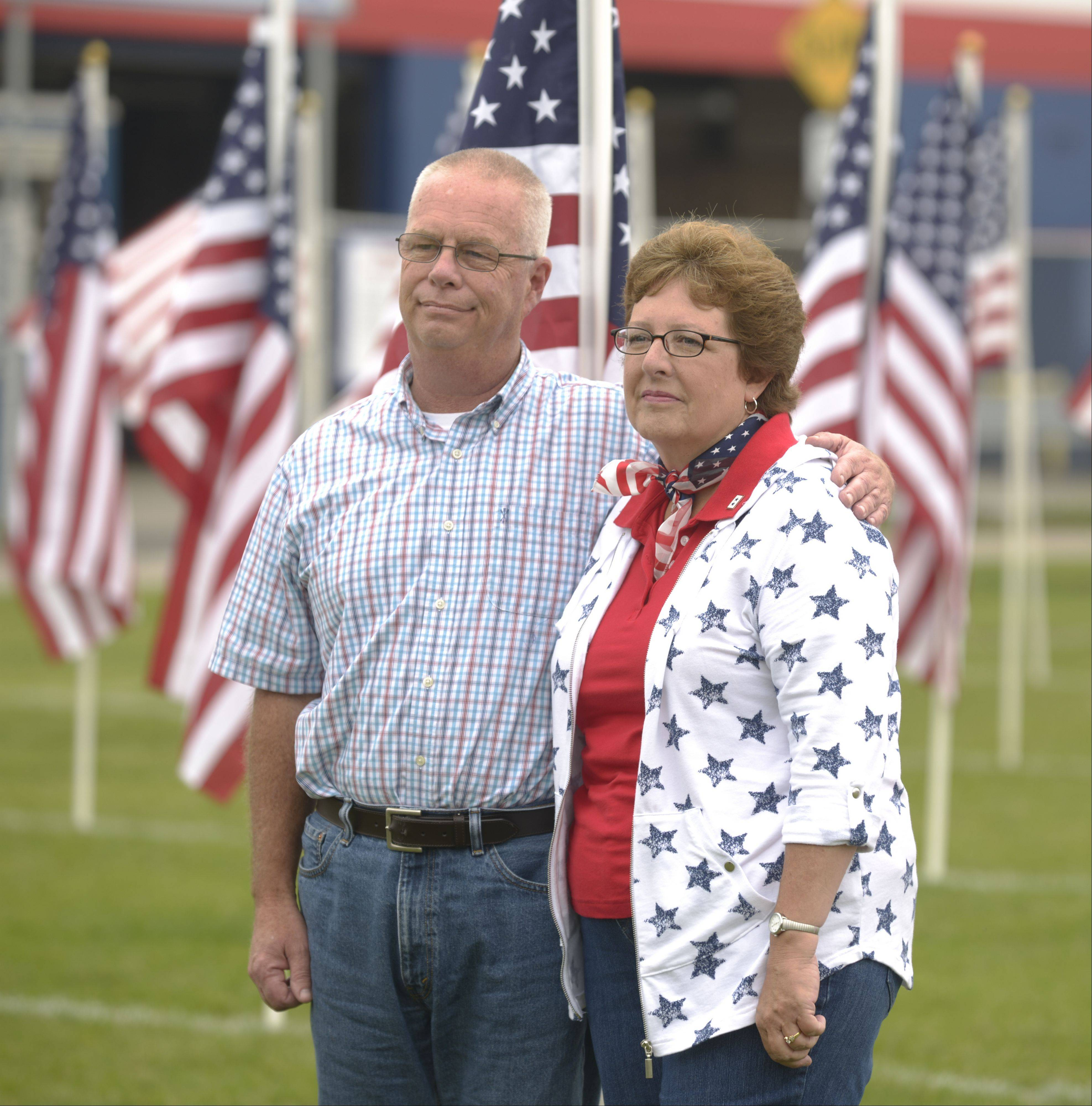 Ron and Debbie Ritter stand among a small field of flags Friday during a ceremony in advance of the Healing Field of Honor to be held Nov. 3 to 13 at West Aurora High School. The Ritters' two sons are in the service, Robert in the Navy and Raymond in the Coast Guard.