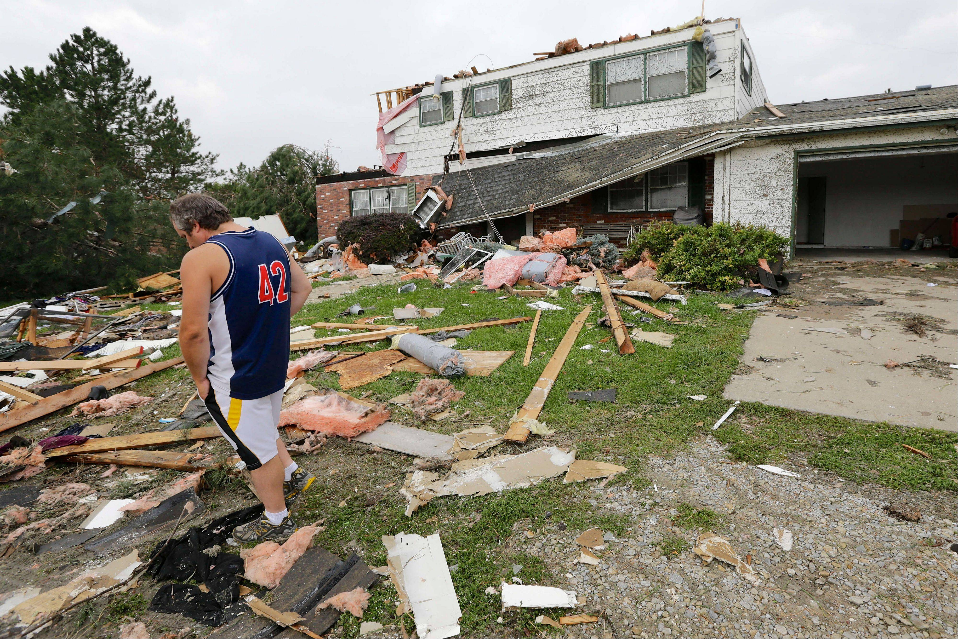 Travis Randall walks through the debris-strewn yard of his parent's home in Hickman, Neb., Friday, Oct. 4, 2013, after it was struck by a tornado. Powerful storms crawled into the Midwest on Friday, dumping heavy snow in South Dakota, spawning a tornado in Nebraska and threatening dangerous thunderstorms from Oklahoma to Wisconsin.