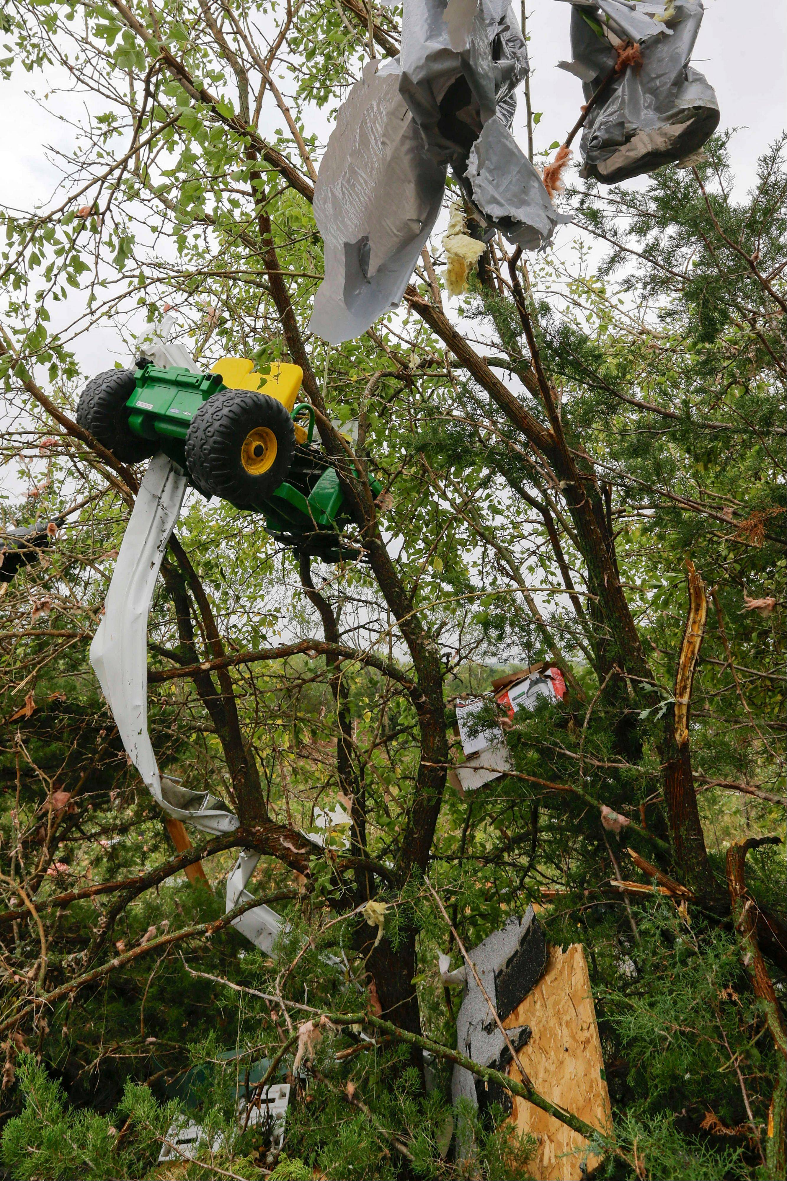 Debris, including a toy tractor, are trapped in a tree following a tornado in Hickman, Neb., Friday, Oct. 4, 2013. Powerful storms crawled into the Midwest on Friday, dumping heavy snow in South Dakota, spawning a tornado in Nebraska and threatening dangerous thunderstorms from Oklahoma to Wisconsin.
