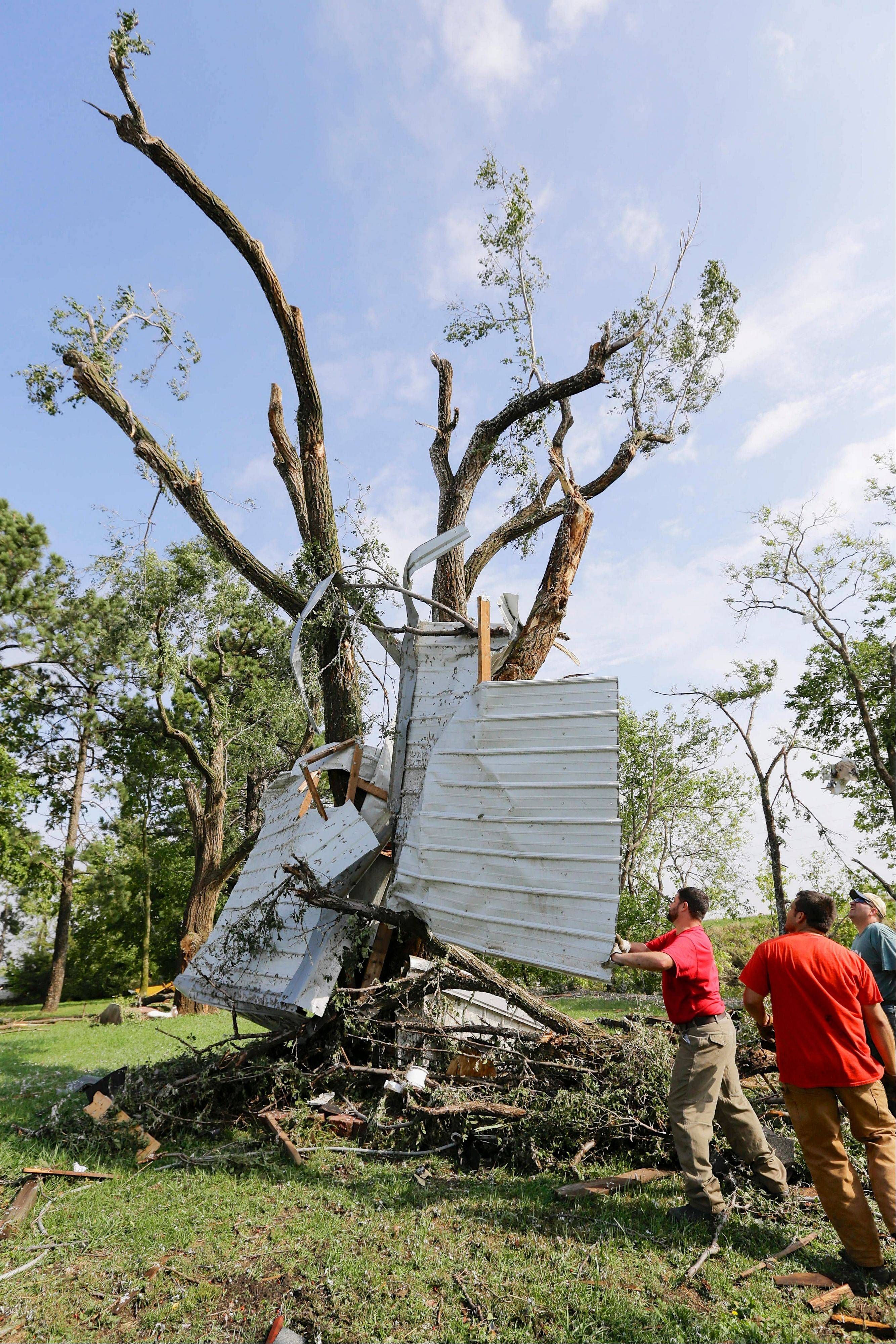 Residents try to free a house panel from where it was lodged against a tree following a tornado in Bennet, Neb., Friday, Oct. 4, 2013. Powerful storms crawled into the Midwest on Friday, dumping heavy snow in South Dakota, spawning a tornado in Nebraska and threatening dangerous thunderstorms from Oklahoma to Wisconsin.