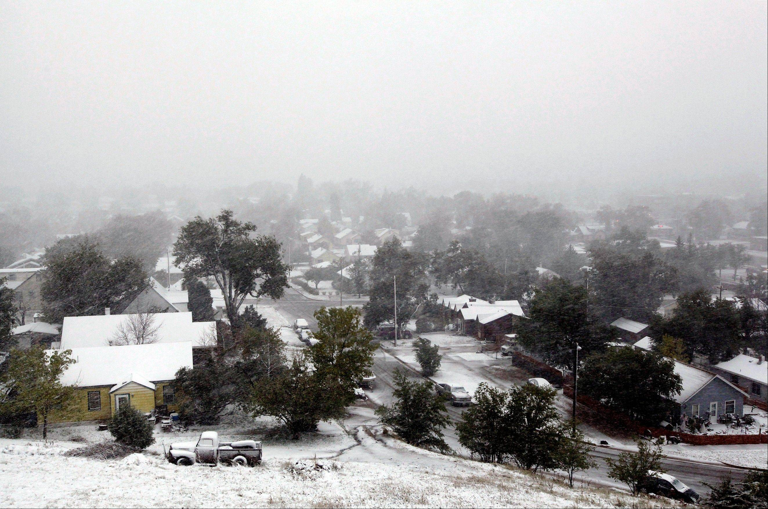 Snow falls over a residential neighborhood during a storm Friday, Oct. 4, 2013, in Rapid City, S.D. Blizzards rolled into parts of Wyoming and South Dakota on Friday, bringing the states to an unseasonably early wintery standstill by closing highways and schools.