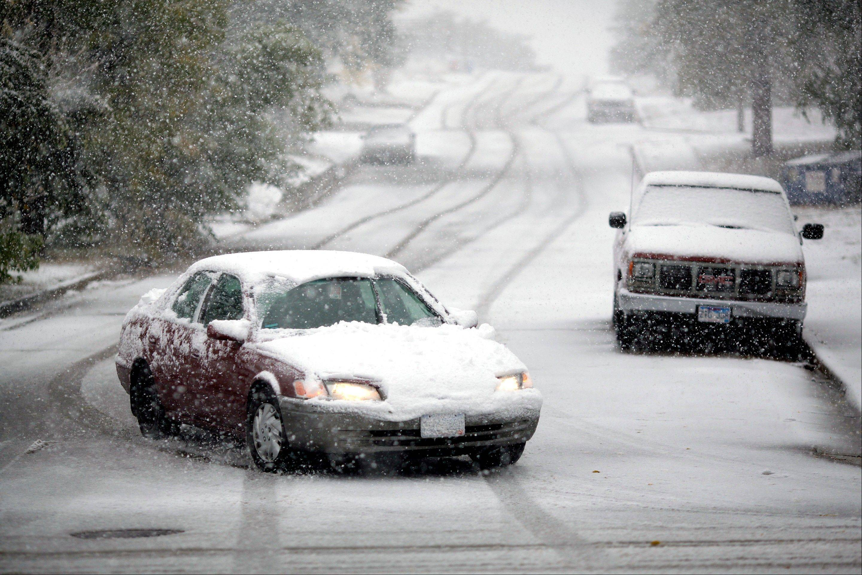 Motorists make their way down 6th Street during a snowstorm Friday, Oct. 4, 2013, in Rapid City, S.D. Blizzards rolled into parts of Wyoming and South Dakota on Friday, bringing the states to an unseasonably early wintery standstill by closing highways and schools.