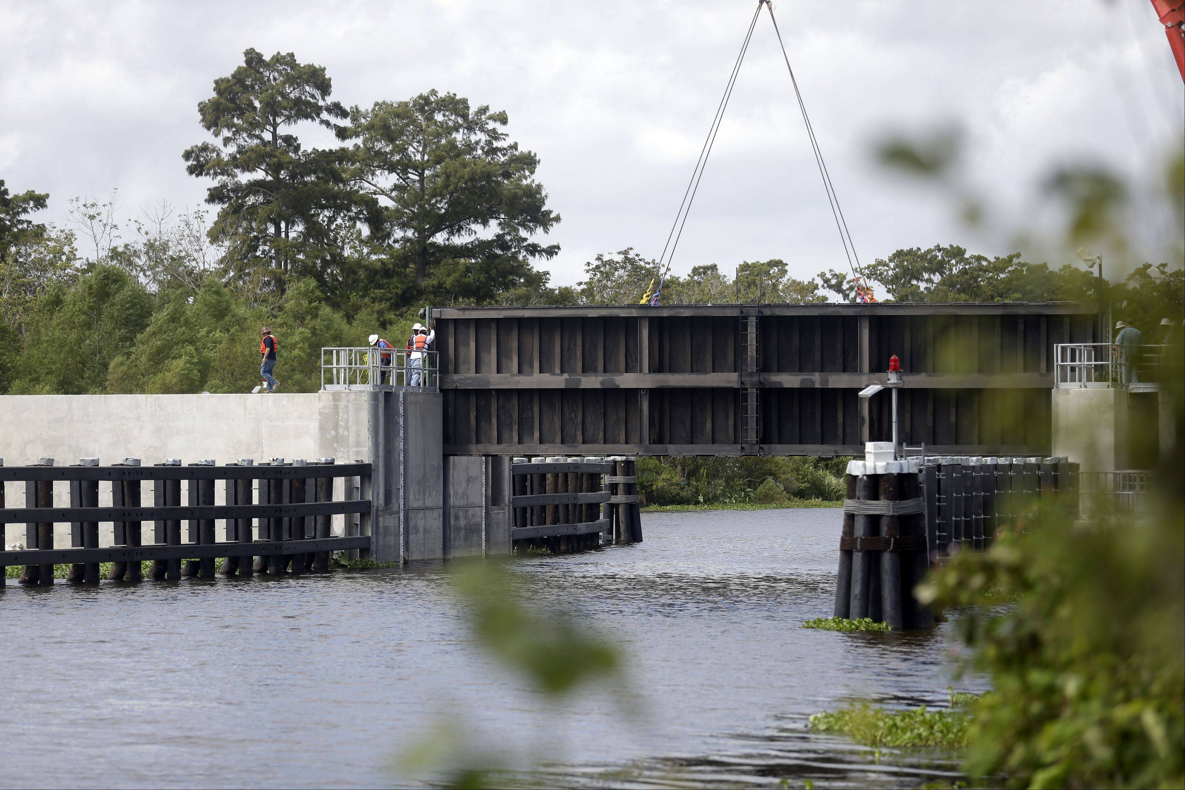 A crane lowers a flood gate into Hero Canal, as part of the hurricane protection system protecting the greater New Orleans area, in anticipation of Tropical Storm Karen, in Belle Chasse, La., Friday, Oct. 4, 2013.