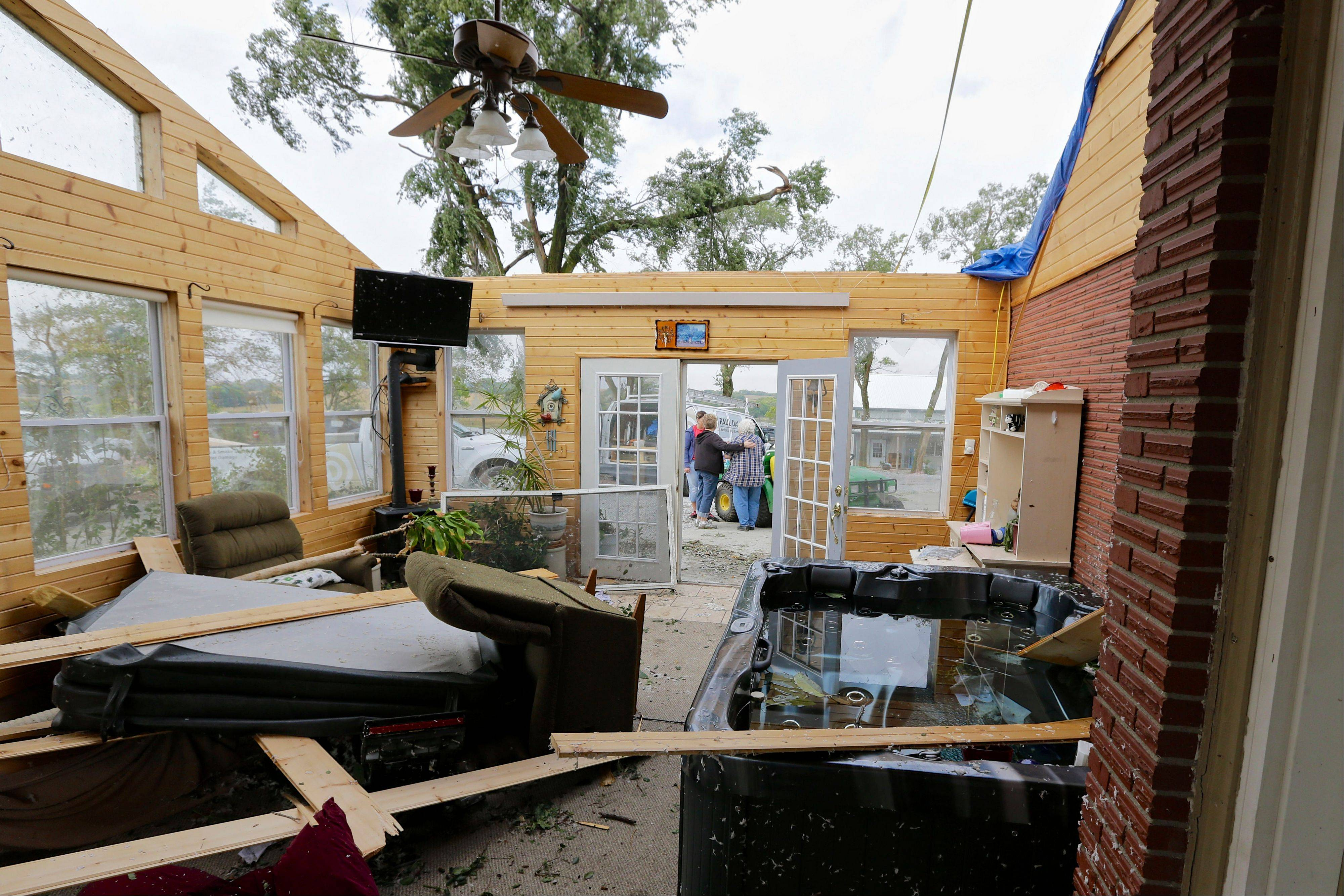 A neighbor comforts Vicki Kempkes, right, after her home was hit by a tornado in Bennet, Neb., Friday, Oct. 4, 2013. Powerful storms crawled into the Midwest on Friday, dumping heavy snow in South Dakota, spawning a tornado in Nebraska and threatening dangerous thunderstorms from Oklahoma to Wisconsin.