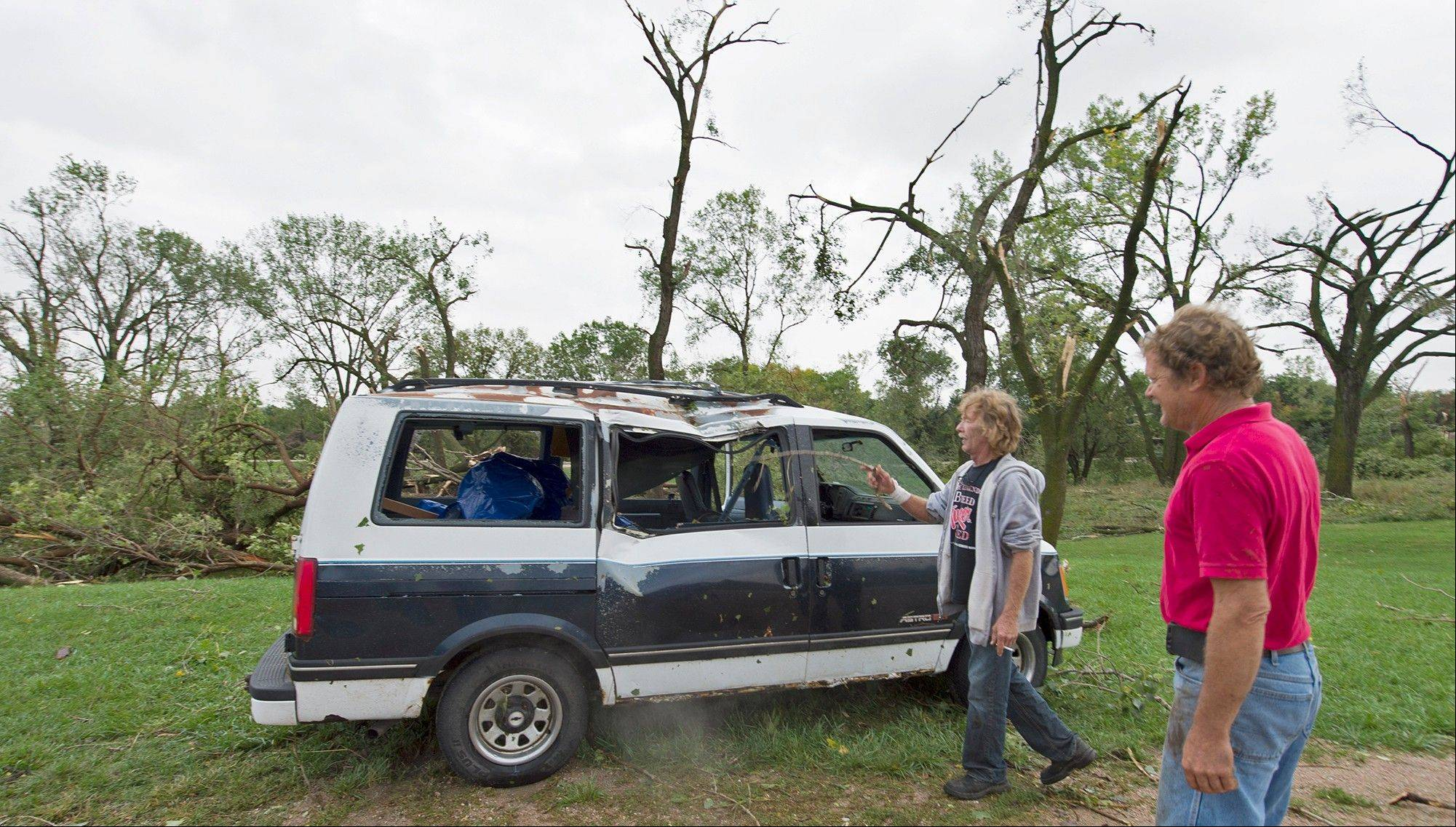 Jim Stoddard, left, and his brother-in-law Todd Harlan check out Jim's van on Friday, Oct. 4, 2013 in Hickman, Neb. Powerful storms crawled into the Midwest on Friday, dumping heavy snow in South Dakota, spawning a tornado in Nebraska and threatening dangerous thunderstorms from Oklahoma to Wisconsin.