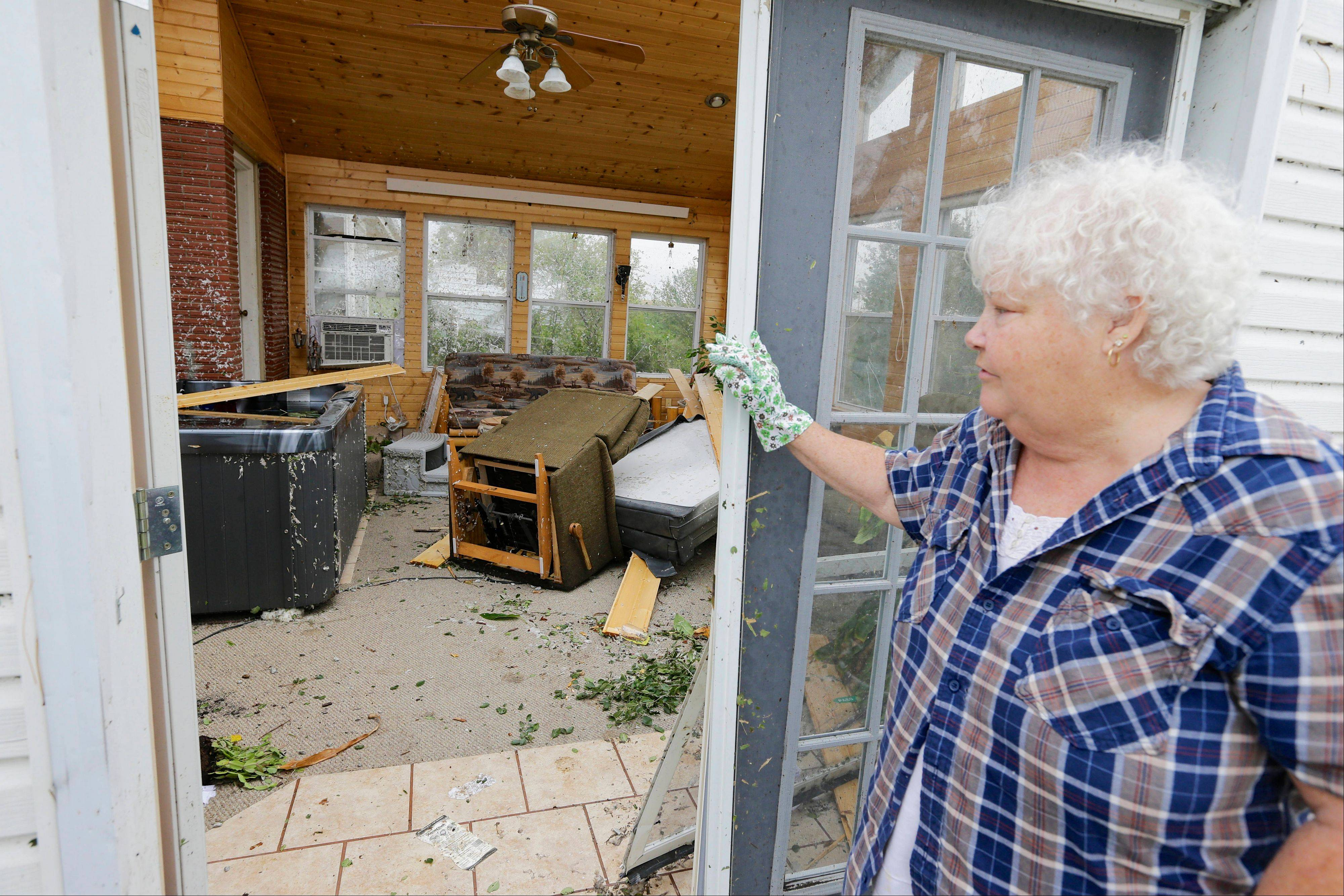 Vicki Kempkes looks over her destroyed recreation room in Bennet, Neb., Friday, Oct. 4, 2013. Powerful storms crawled into the Midwest on Friday, dumping heavy snow in South Dakota, spawning a tornado in Nebraska and threatening dangerous thunderstorms from Oklahoma to Wisconsin.