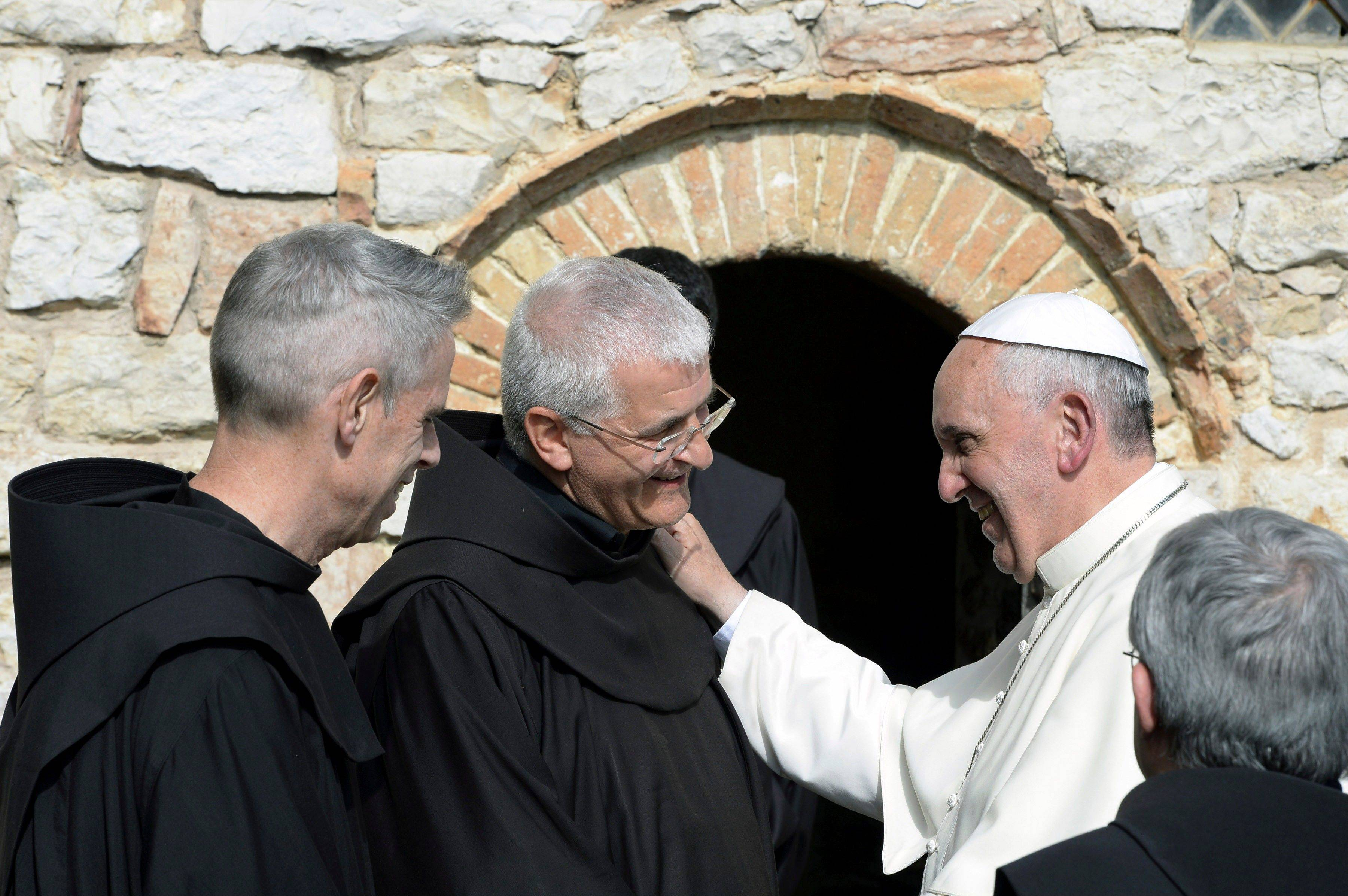 Pope Francis, right, shares a word with friars during his tour of the Eremo delle Carceri hermitage, near Assisi, Italy, Friday, Oct. 4, 2013. Pope Francis took a pilgrimage to his namesake's hometown Friday, urging the faithful to follow the example of the 13th-century St. Francis, who renounced a wealthy, dissolute lifestyle to embrace a life of poverty and service to the poor.