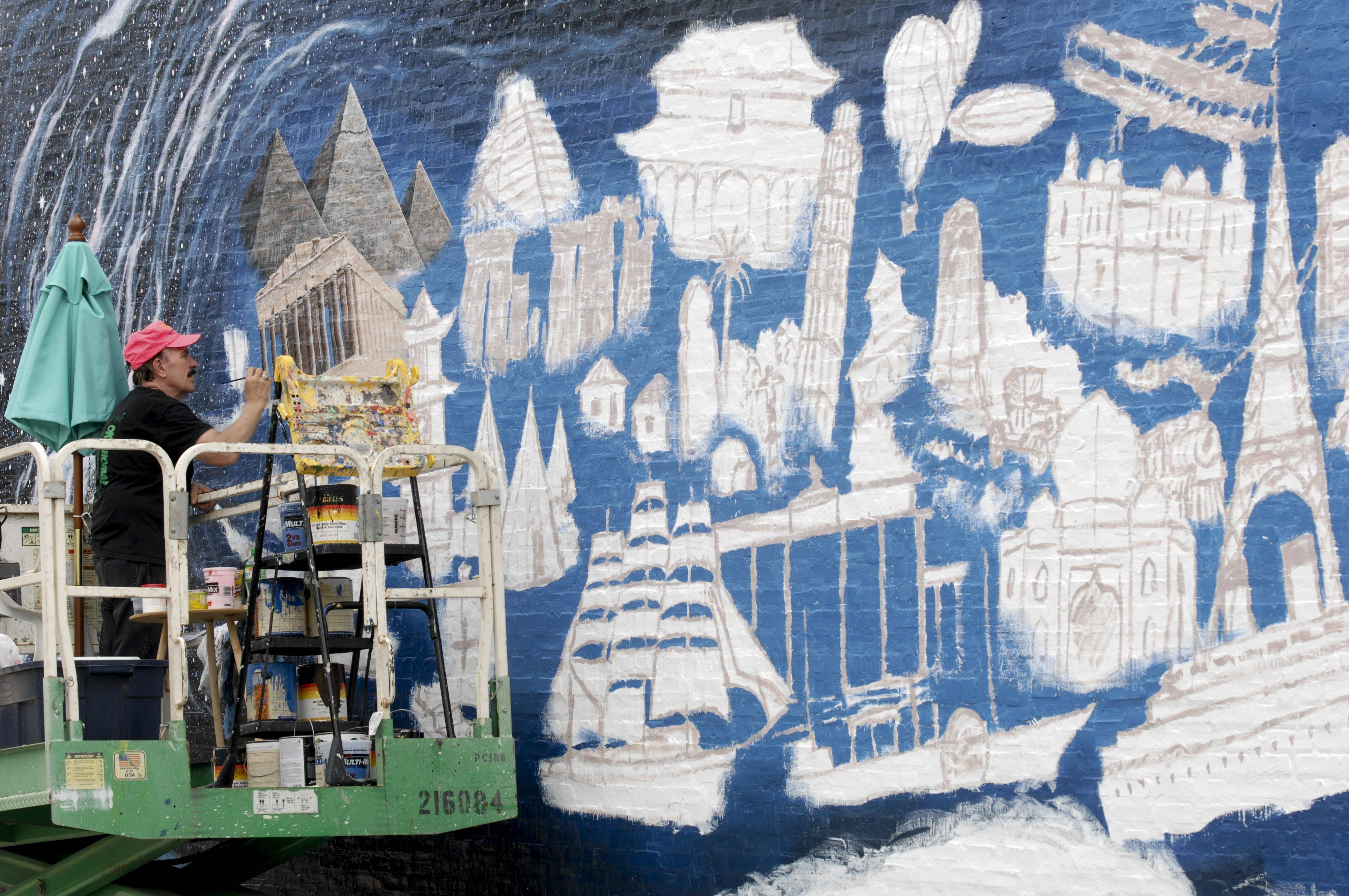 "Artist R.J. Ogren works on a mural ""Pearls of the Universe"" on a 16x70 foot brick wall at 1026 College Ave., Wheaton. The mural is inspired by a poem by Wheaton resident Mehret Asgedom."