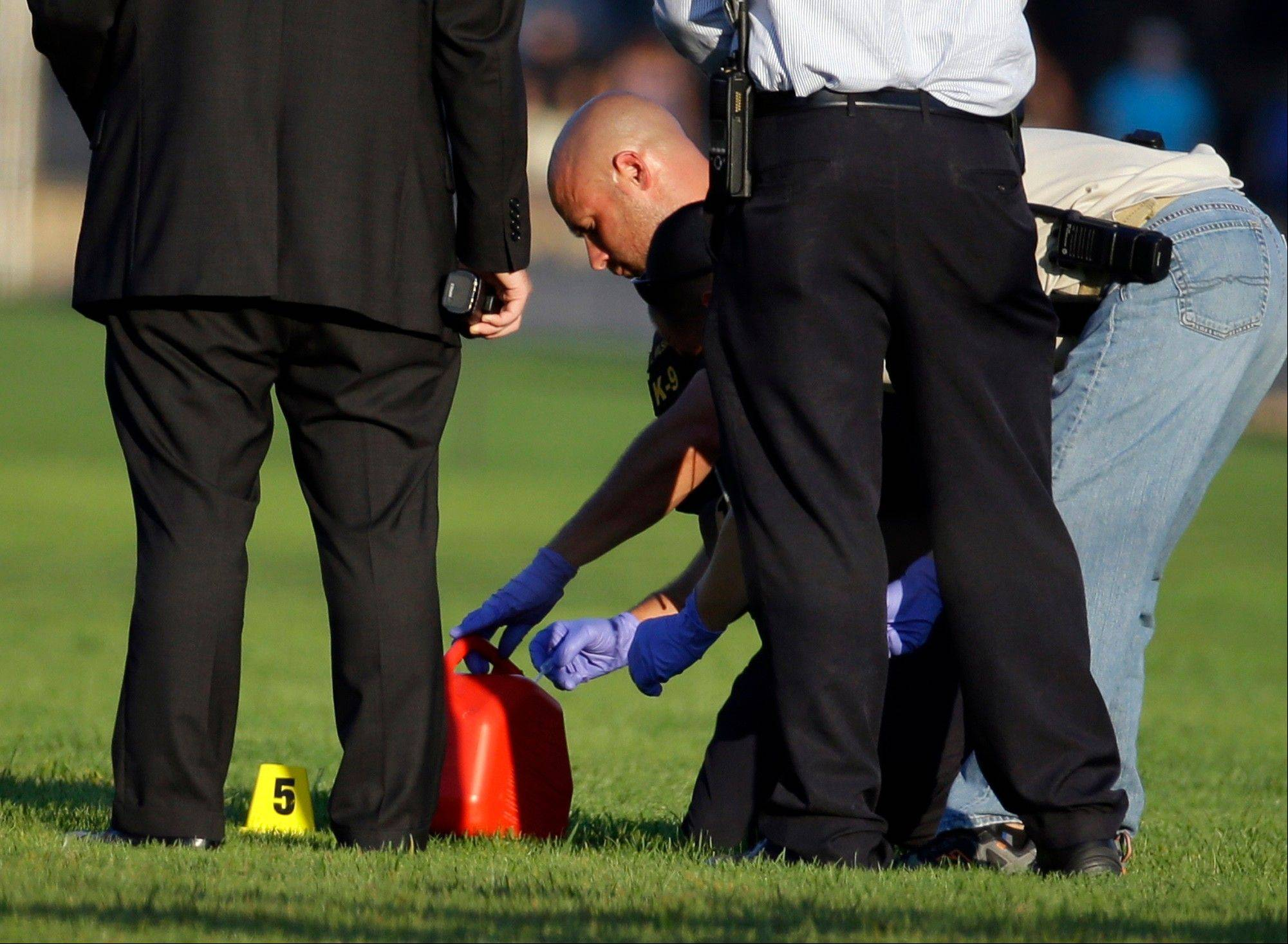 Police investigators take a sample from a red container near where officials said a man set himself on fire, on the National Mall, Friday, Oct. 4, 2013, in Washington.