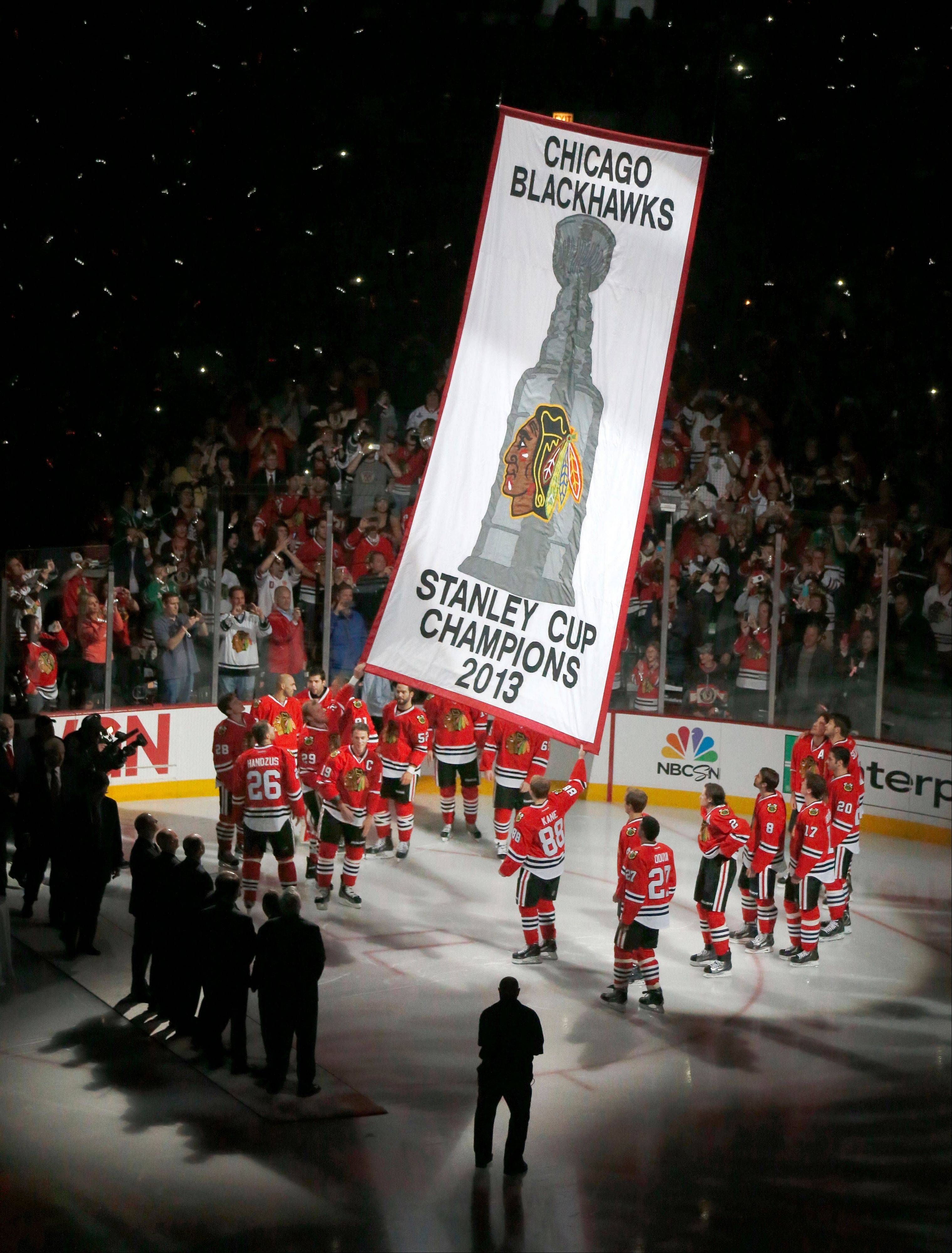 The Blackhawks watch as the Stanley Cup Championship banner is lifted to the rafters during ceremonies before an NHL hockey game between the Blackhawks and the Washington Capitals Tuesday, Oct. 1, 2013, in Chicago.
