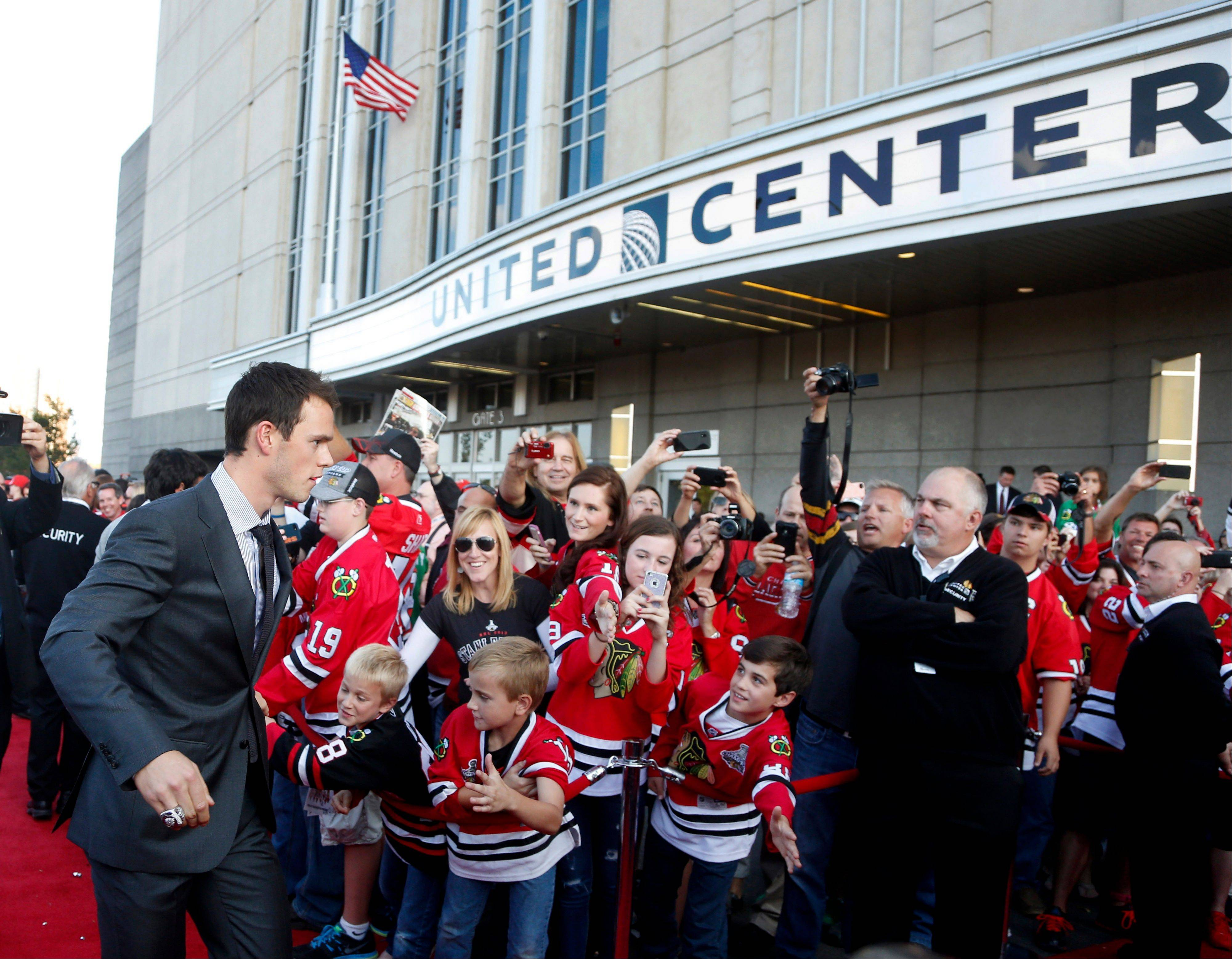 Blackhawks' center Jonathan Toews walks the red carpet outside the United Center as the team arrives for their season-opening NHL hockey game against the Washington Capitals Tuesday, Oct. 1, 2013, in Chicago.
