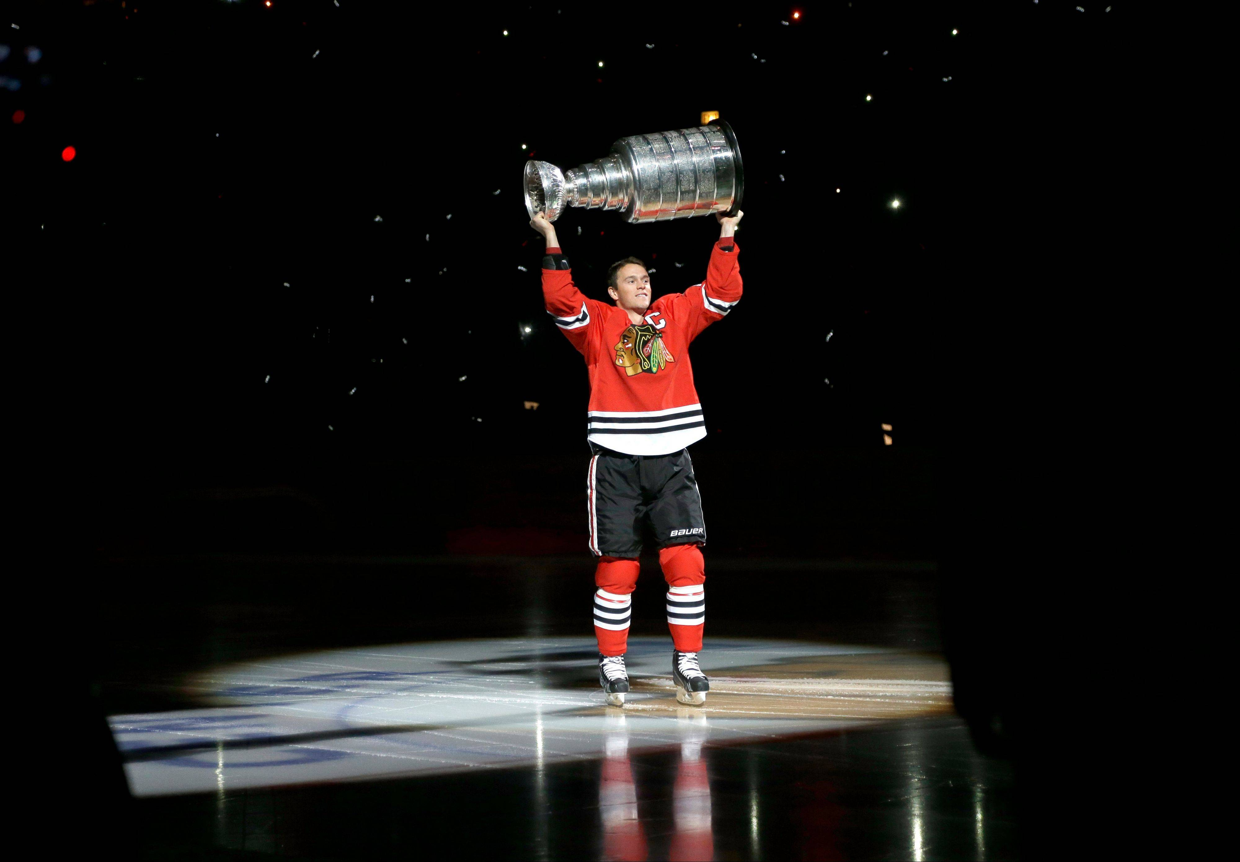 Blackhawks center Jonathan Toews carries out the Stanley Cup during a banner raising ceremony before an NHL hockey game between the Blackhawks and the Washington Capitals, Tuesday, Oct. 1, 2013, in Chicago.