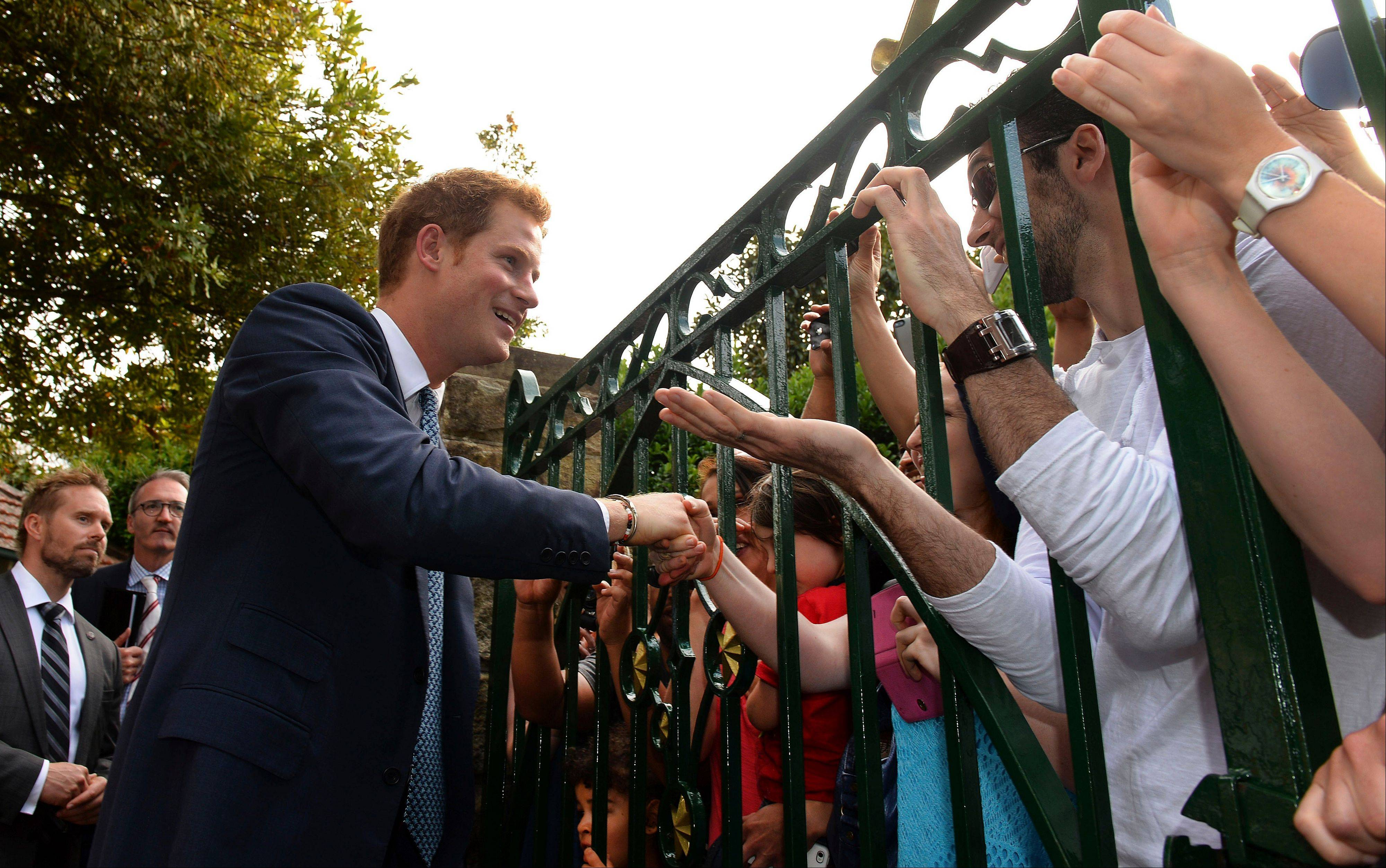 Associated Press Britain's Prince Harry, left, greets well-wishers at the gates to Kirribilli House, the prime minister's residence in Sydney, Saturday, Oct. 5. Harry, fourth in line to the British throne, is in Australia's largest city for just one day as part of a quick trip Down Under.