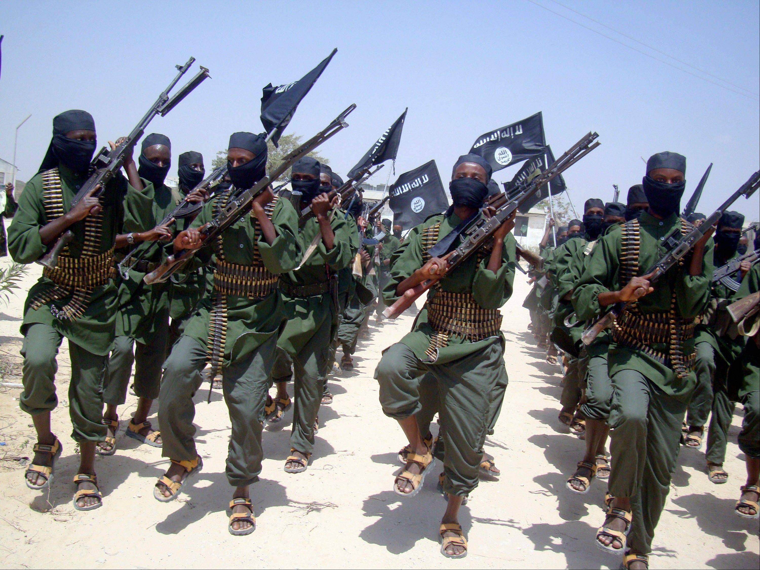 In this Thursday, Feb. 17, 2011 photo, al-Shabab fighters march with their weapons during military exercises on the outskirts of Mogadishu, Somalia. Foreign military forces carried out a pre-dawn strike Saturday, Oct. 5, against foreign fighters in the same southern Somalia village where U.S. Navy SEALS four years ago killed a most-wanted al-Qaida operative, officials said.