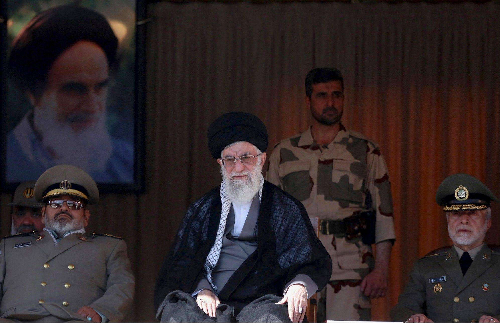 "In this picture released by an official website of the office of the Iranian supreme leader, Supreme Leader Ayatollah Ali Khamenei, center, attends a graduation ceremony of army cadets, while Chief of the General Staff of Iran's Armed Forces, Gen. Hasan Firouzabadi, left, and army commander Ataollah Salehi, right, accompany him in Tehran, Iran, Saturday, Oct. 5, 2013. Iran's top leader said some aspects of Hassan Rouhani's trip to New York last month were ""not appropriate,"" but has reiterated his crucial support for the president's policy of outreach to the West. A portrait of the late revolutionary founder Ayatollah Khomeini hangs in the background. (AP Photo/Office of the Iranian Supreme Leader)"
