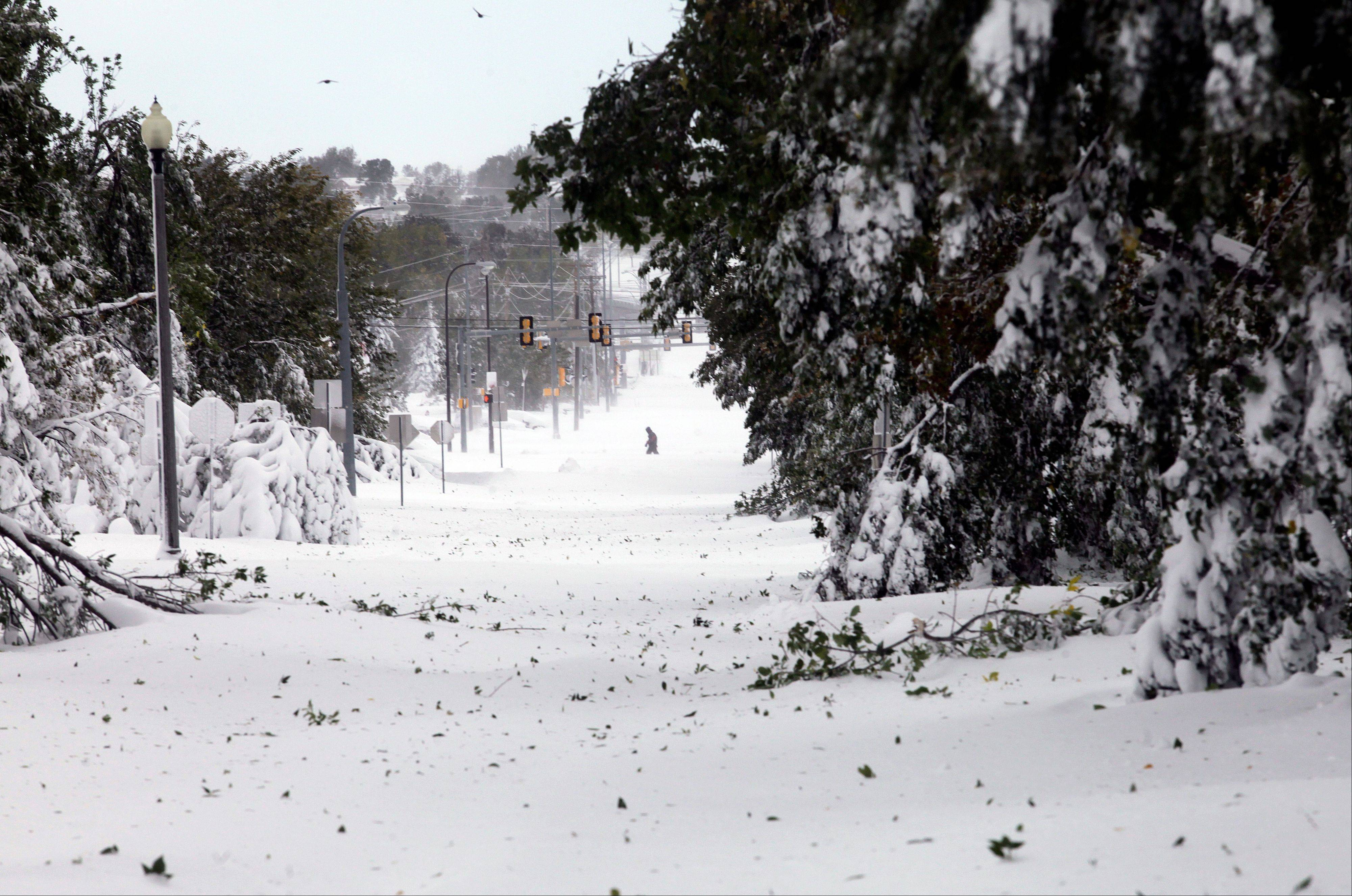 A pedestrian walks by West Boulevard in Rapid City, S.D,, Saturday, Oct. 5. South Dakota emergency agencies are asking snowmobile operators in the Rapid City area to help find motorists stranded by an autumn storm. The National Weather Service says the storm dumped at least three and a half feet of wet, heavy snow in the Black Hills. Rapid City had 21 inches, but 31 inches was recorded just a mile southwest of the city.