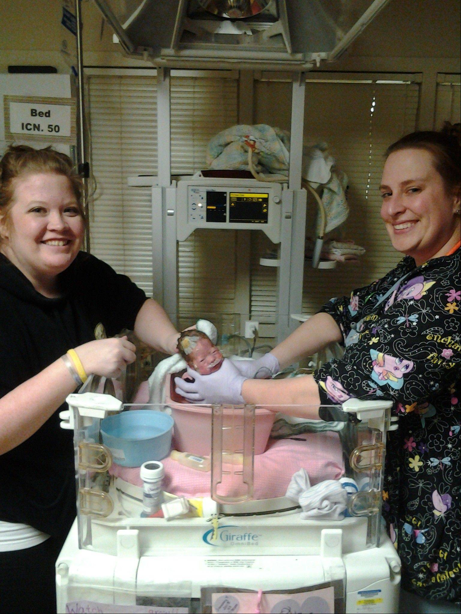 Amy Wilk, left, of Elk Grove Village helps bathe her daughter, Olivia, born two months early, with St. Alexius Medical Center neonatal intensive care unit nurse Theresa Brown.