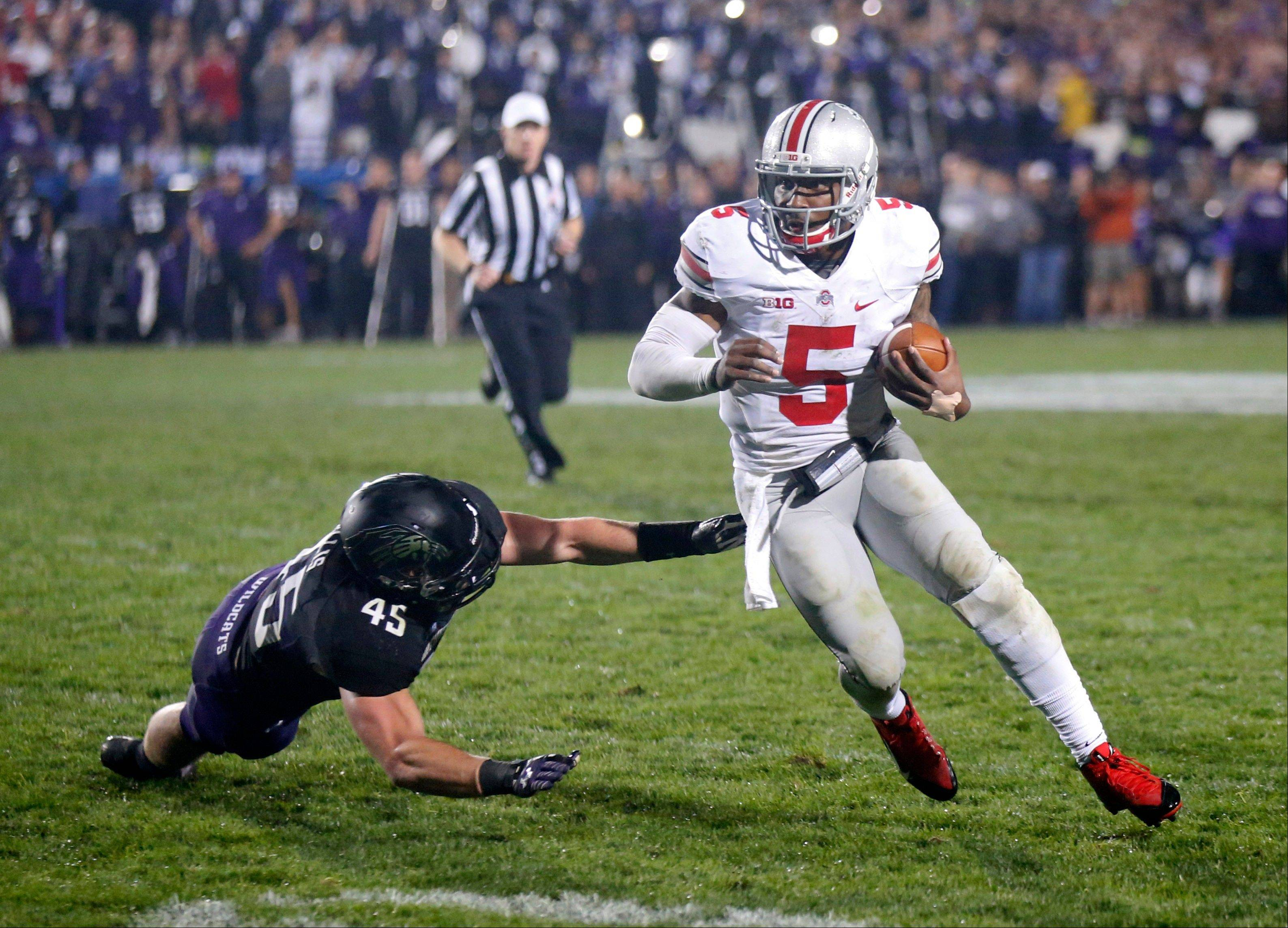 Ohio State quarterback Braxton Miller (5) runs past the outstretched hand of Northwestern linebacker Collin Ellis (45) during Saturday�s game in Evanston. Ohio State won 40-30.
