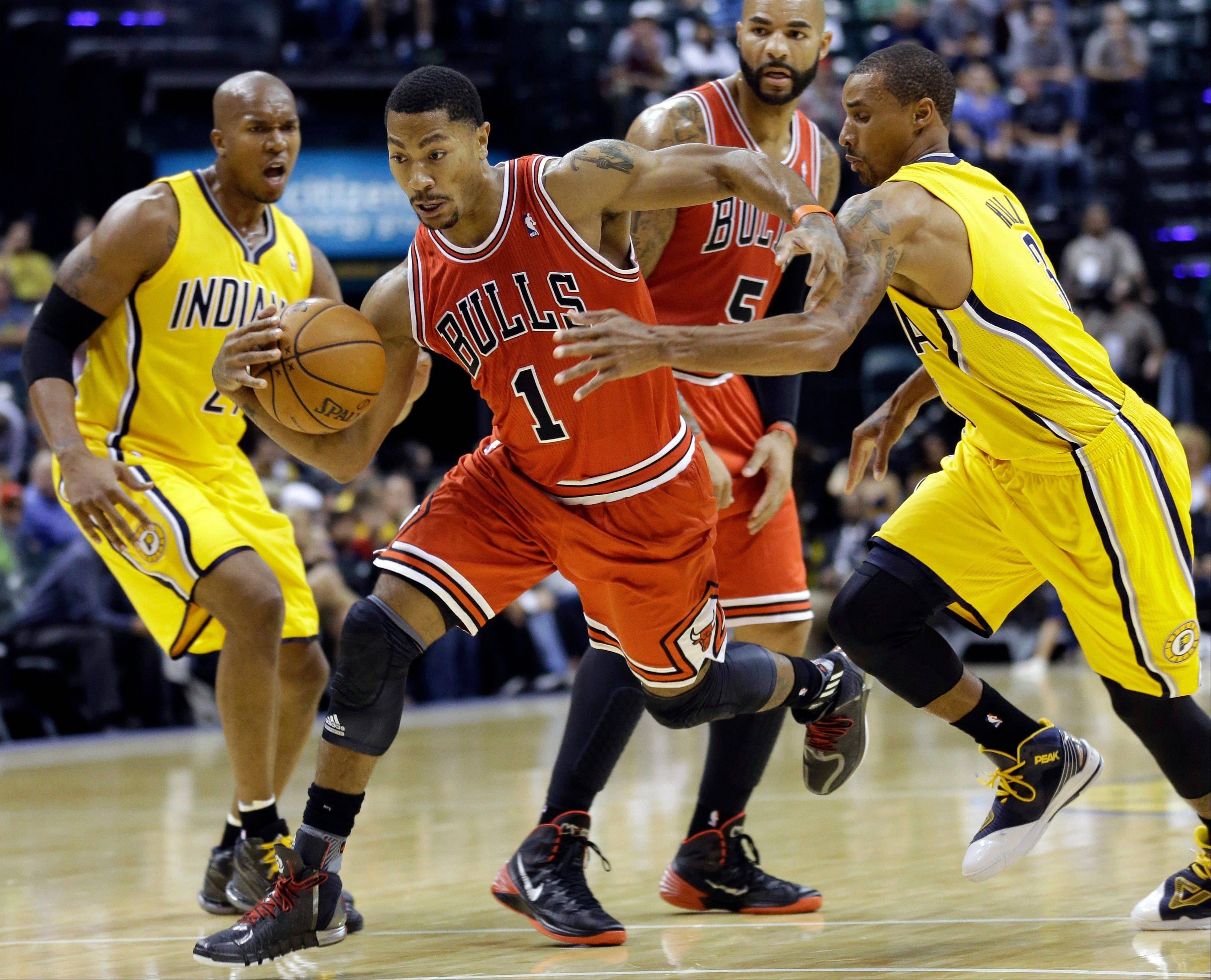 Bulls guard Derrick Rose, playing in his first game since April 28, 2013, cuts between Pacers guard George Hill, right, and power forward David West during Saturday night�s preseason action.
