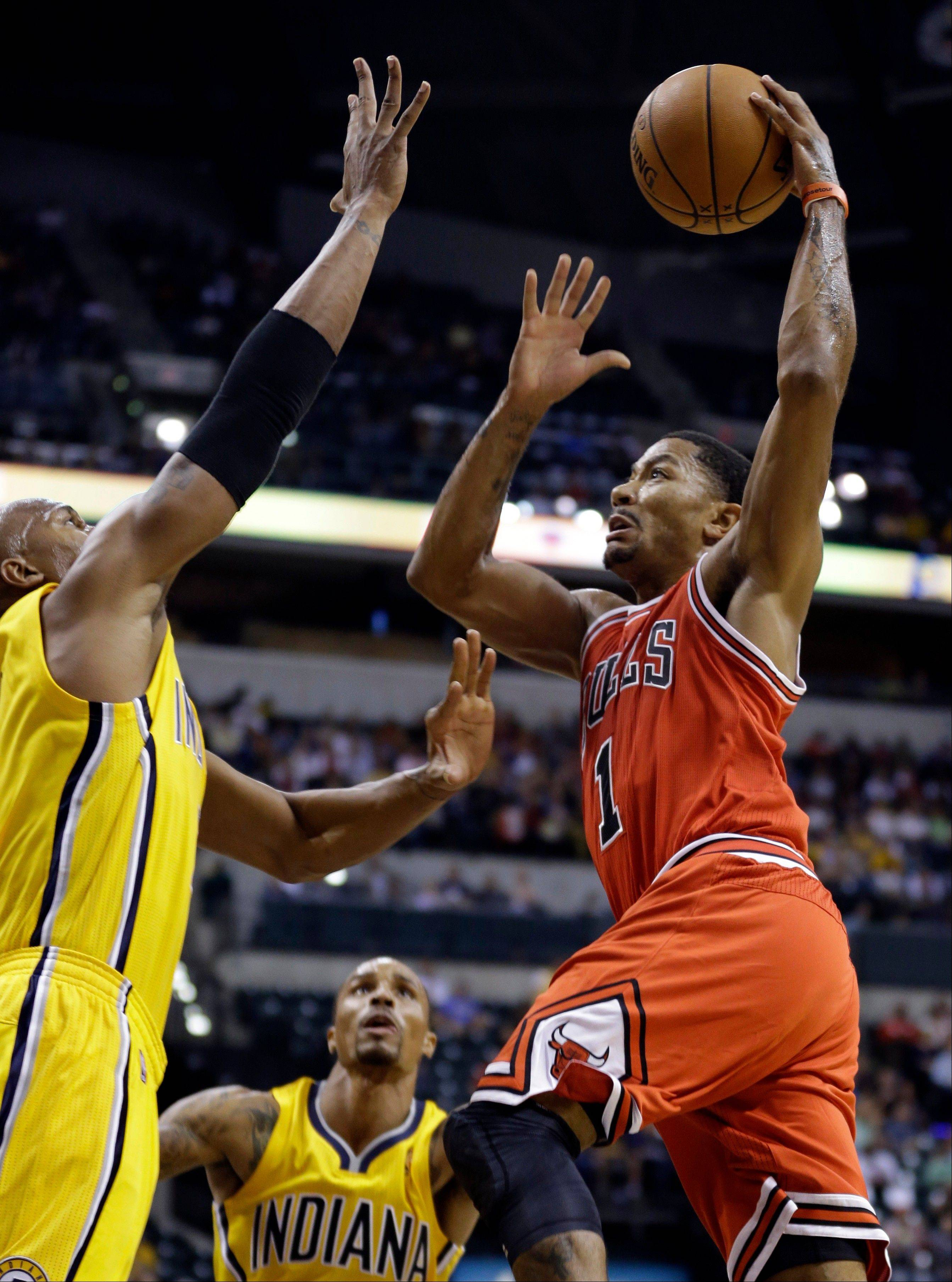 Chicago Bulls guard Derrick Rose, right, goes up for a shot over Indiana Pacers forward David West, left, in the first half of an NBA preseason basketball game Saturday in Indianapolis.