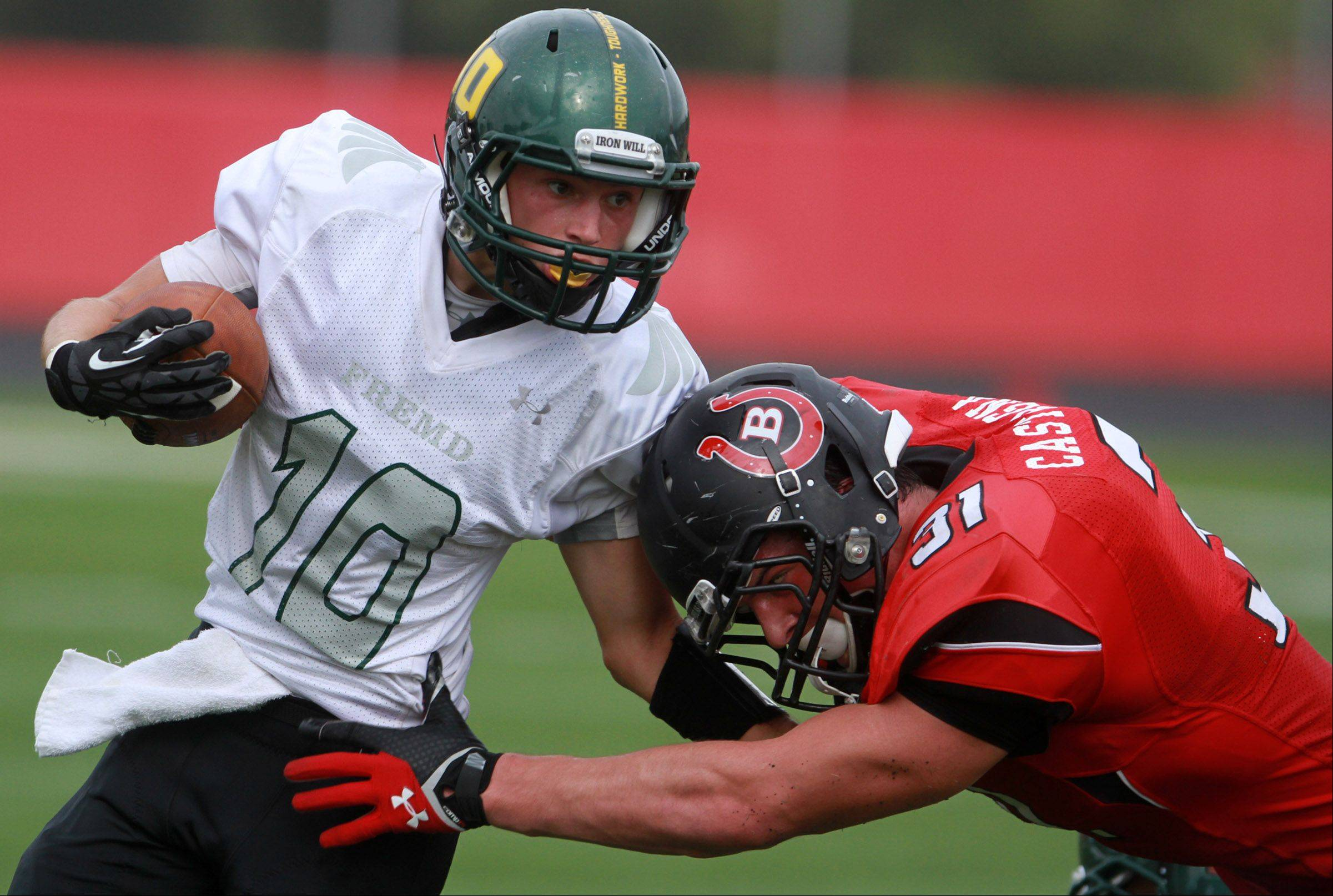 Fremd wide-receiver Anthony Halvorsen is pulled down by Barrington defender Colin Castagna at Barrington on Saturday,October 5.