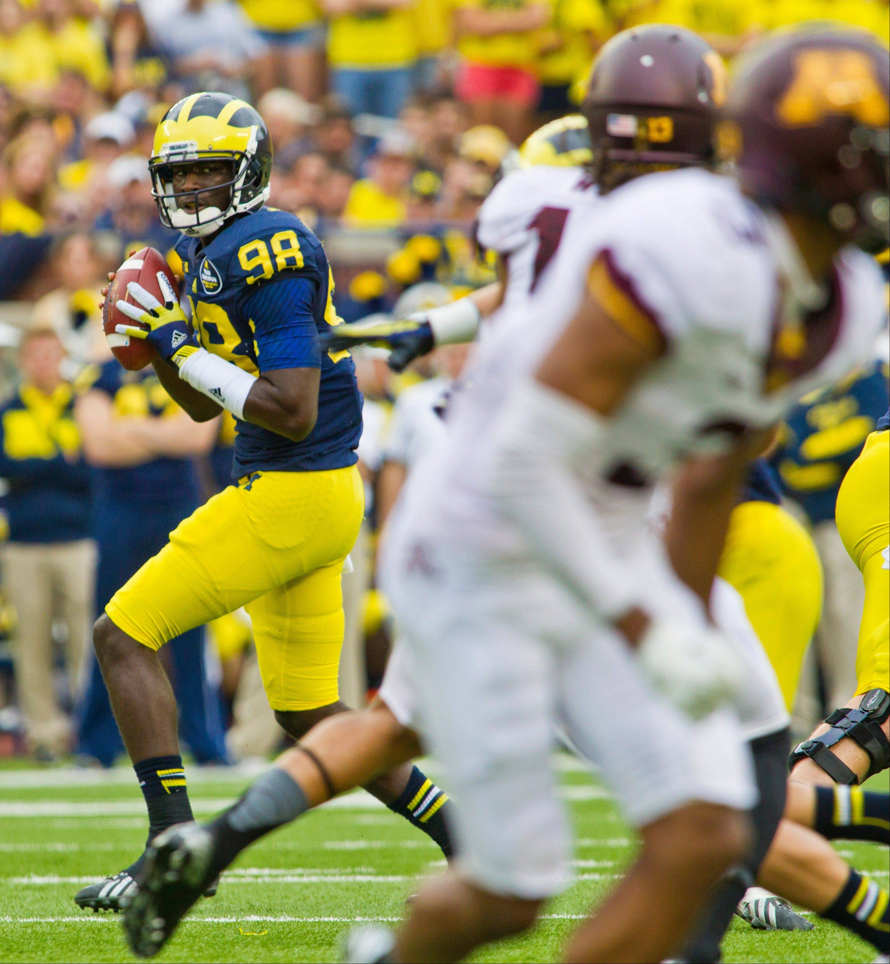 Michigan quarterback Devin Gardner (98) looks for an open receiver to throw a pass to during the second quarter of an NCAA college football game against Minnesota, Saturday, Oct. 5, 2013, in Ann Arbor, Mich. (AP Photo/Tony Ding)