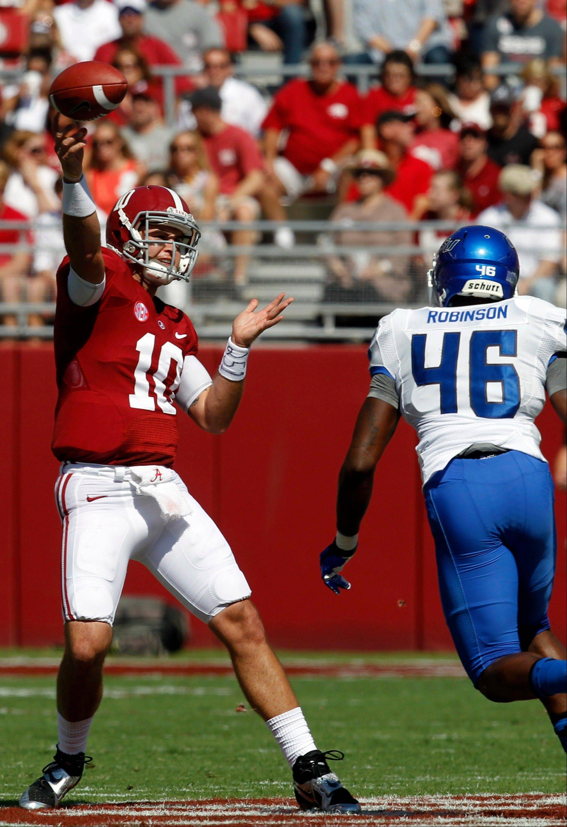 Alabama quarterback AJ McCarron (10) throws a pass while under pressure from Georgia State linebacker Jarrell Robinson (46) during the first half of an NCAA college football game on Saturday, Oct. 5, 2013, in Tuscaloosa, Ala. (AP Photo/Butch Dill)