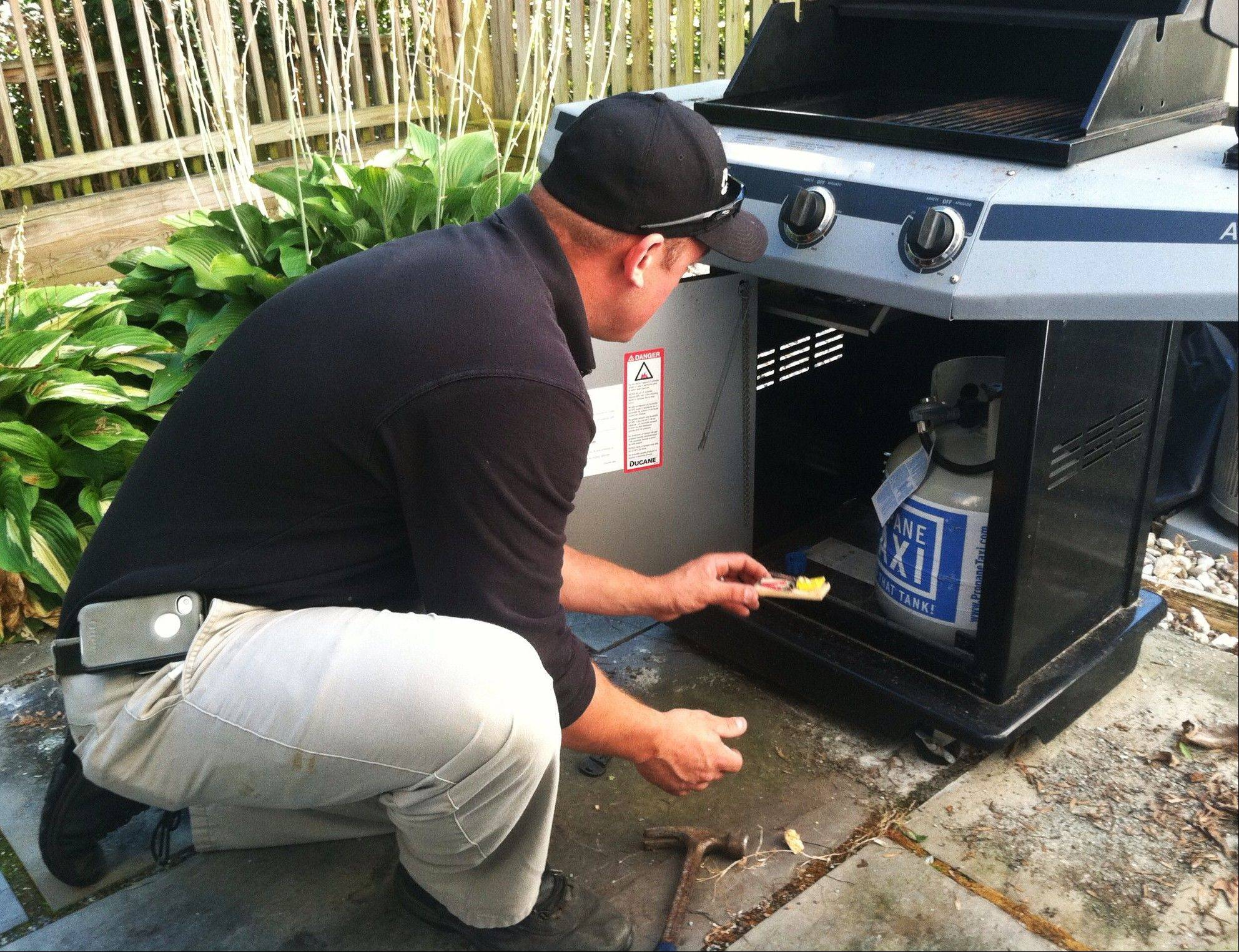 PestNow technician Shane Flanagan sets mouse traps and bait stations on the deck of a home in Rockville, Md.