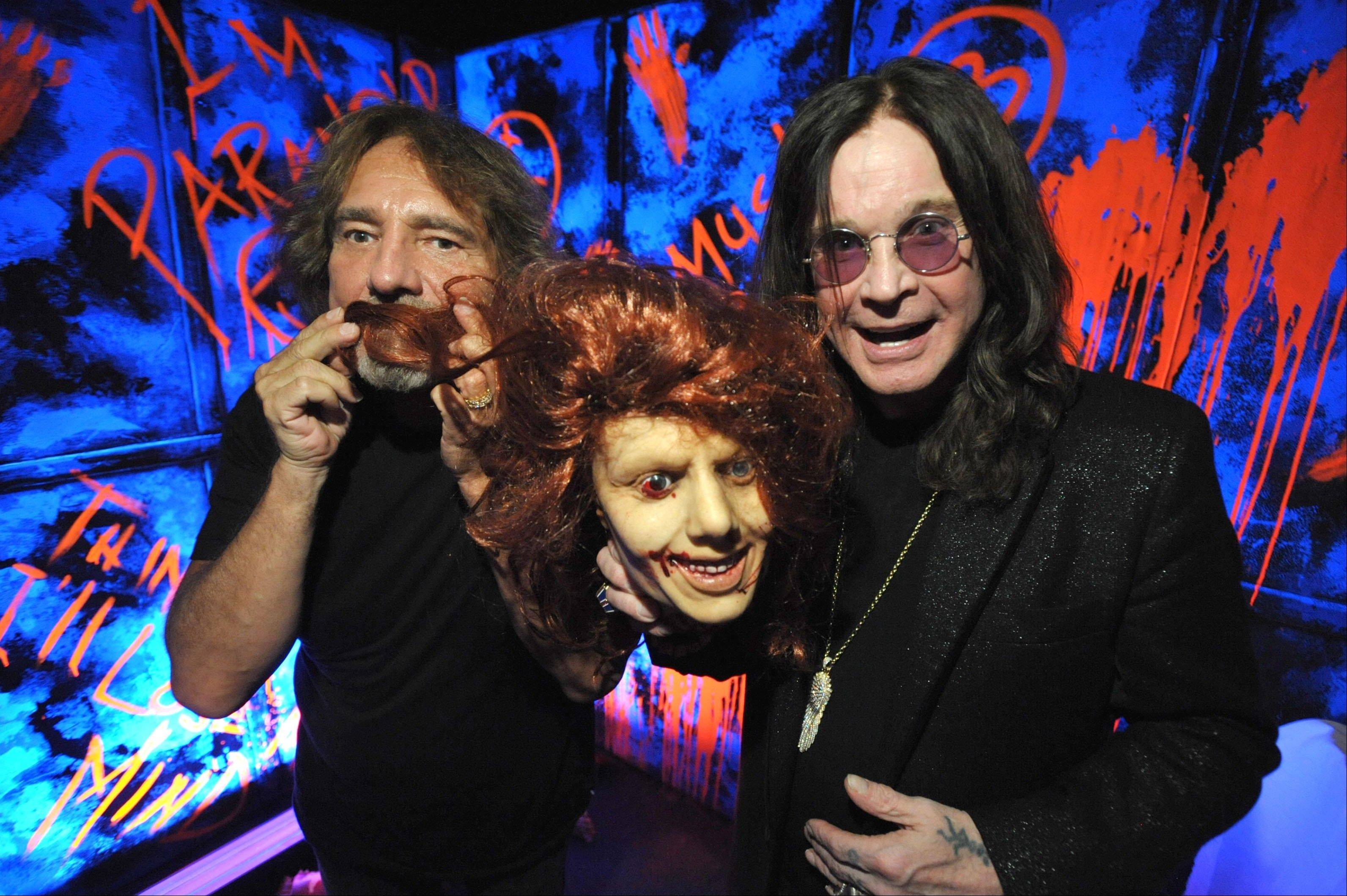 "Geezer Butler, left, and Ozzy Osbourne pose with props at the ""Black Sabbath: 13 3D"" maze at Universal Studios Halloween Horror Nights in Universal City, Calif. Besides ""13"" from Sabbath, there's a ""scare zone"" populated by actors dressed as the nasty Chucky doll from the direct-to-DVD sequel ""Curse of Chucky"" and a new maze incorporating supernatural elements from the ""Insidious"" films."