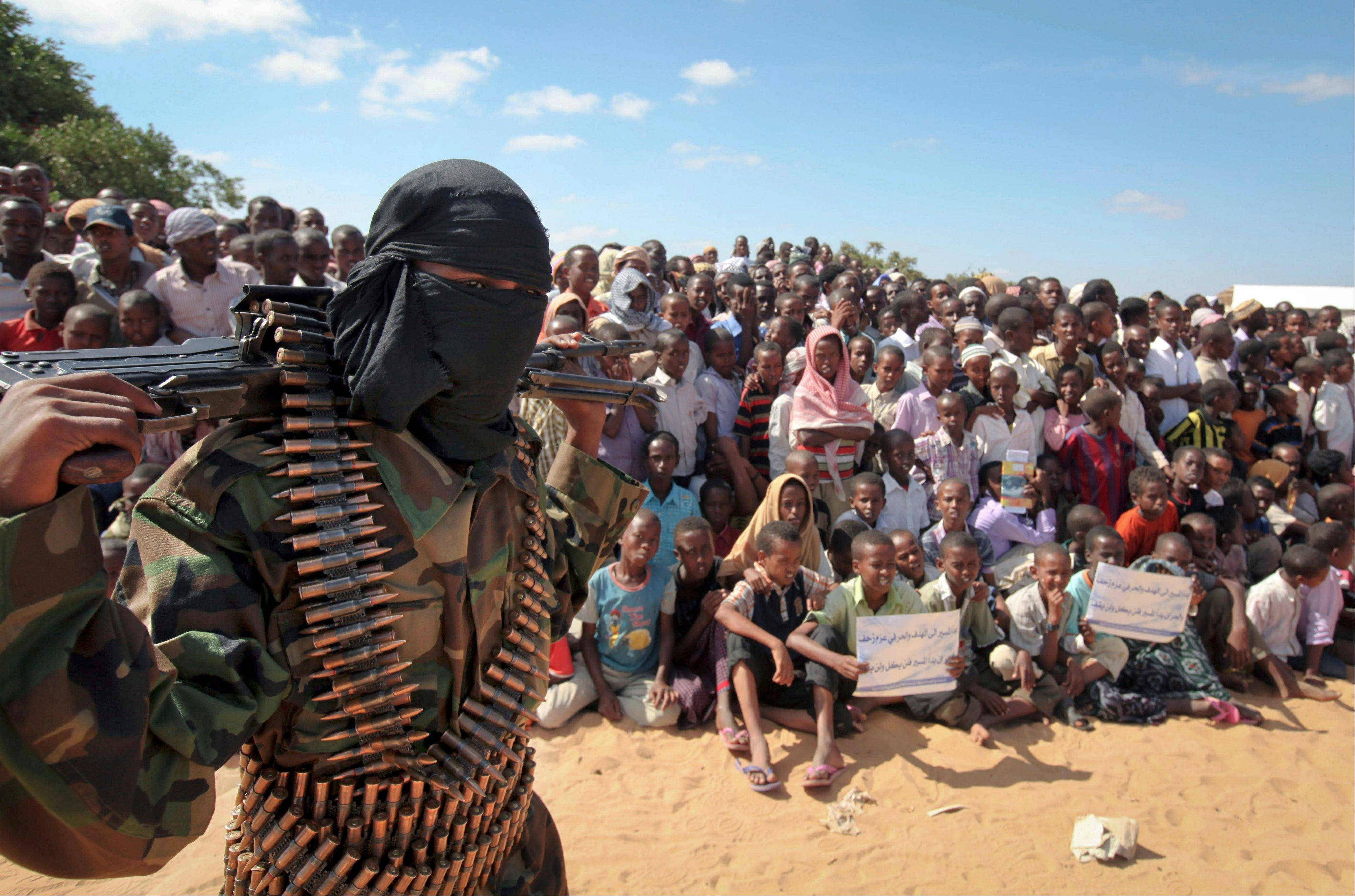 In this Feb. 13, 2012, file photo, an armed member of the militant group al-Shabab attends a rally on the outskirts of Mogadishu, Somalia. International military forces carried out a pre-dawn strike Saturday against foreign fighters in the same southern Somalia village where U.S. Navy SEALS four years ago killed a most-wanted al-Qaida operative, officials said.