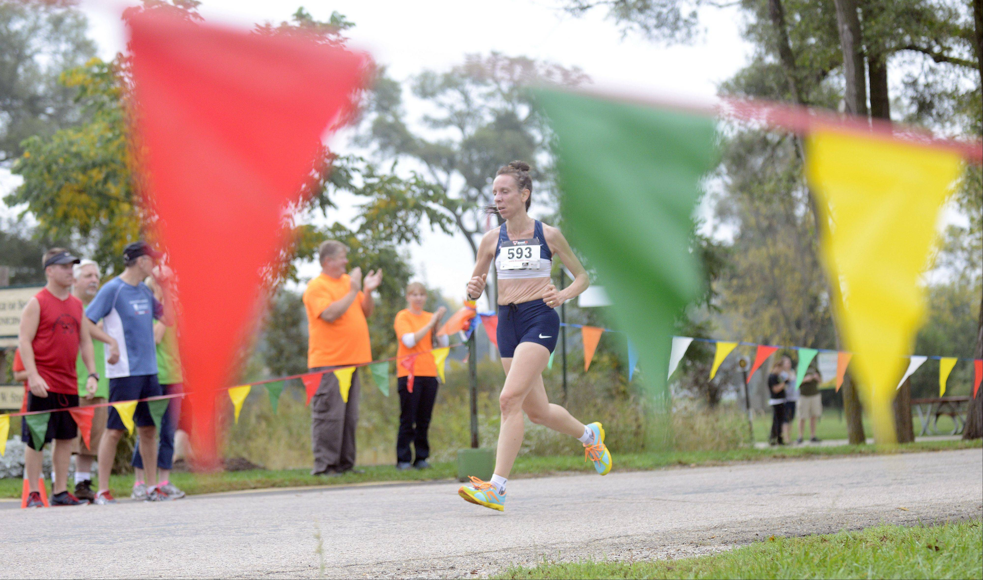 Julie Lee of South Elgin is the first female to cross the finishing line with a time of 33:28.4 in the South Elgin Parks & Recreation FUNdation ninth annual Harvest Hustle 7K Run and 2-Mile Walk on Saturday. Lee has participated in the run for eight years.