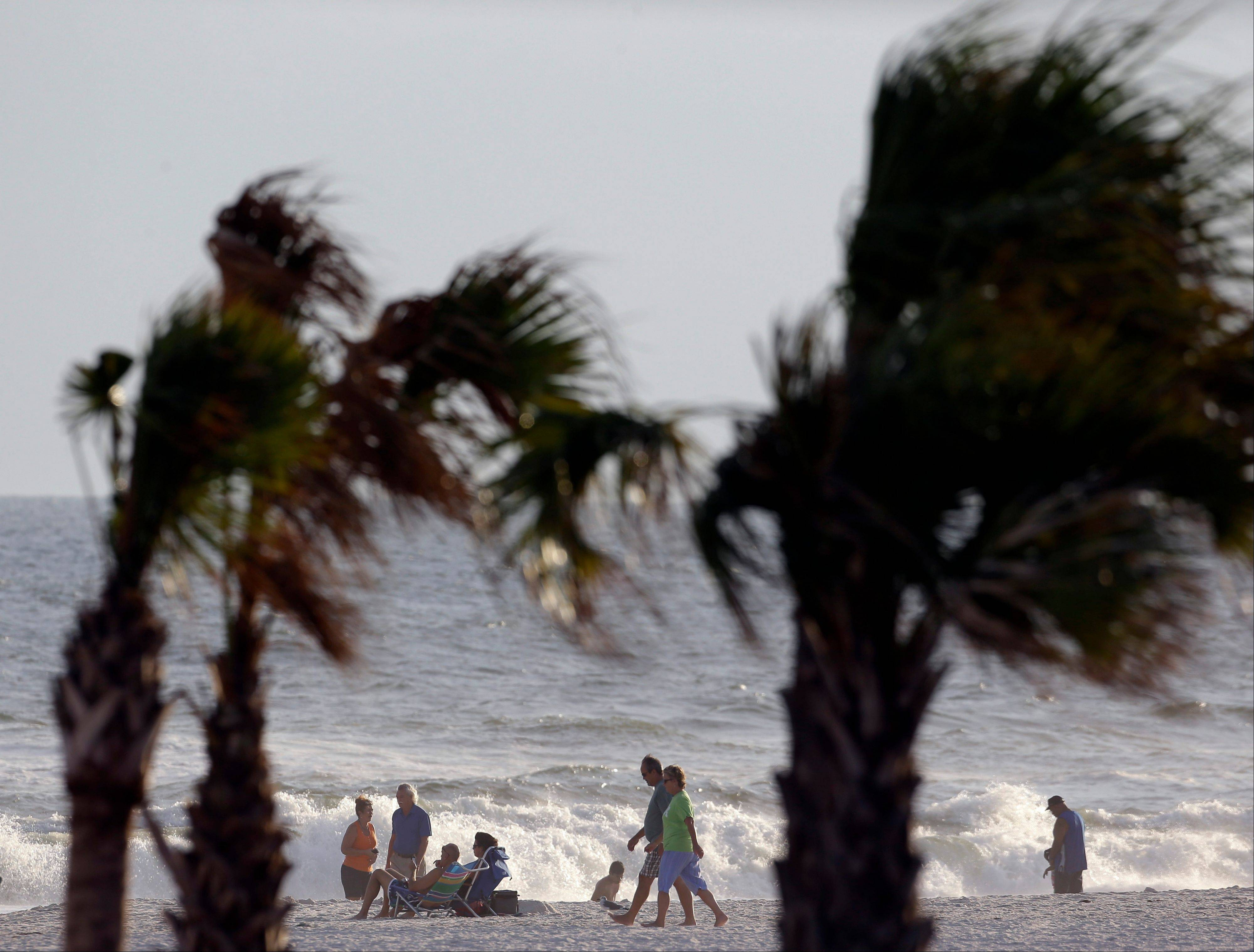 A stiff breeze blows palm trees along the coast in Gulf Shores, Ala., Saturday. Forecasters lifted tropical storm watches along the Alabama coast but surf conditions are still dangerous.