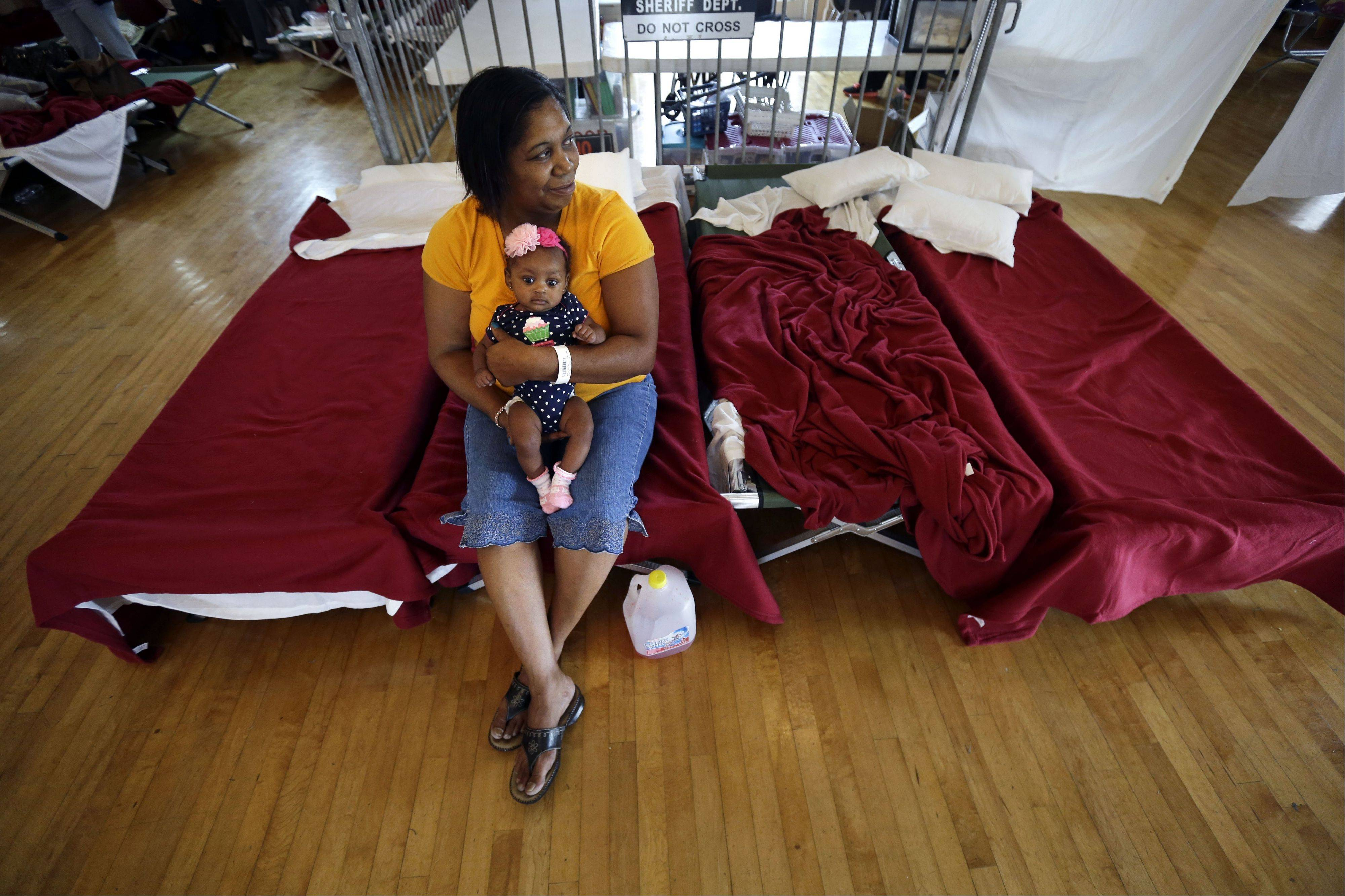 Rhonda Etienne of Davant, La., holds her niece Nevaeh Etienne, three months, in an evacuation shelter in Belle Chasse, La., in anticipation of Tropical Storm Karen, Saturday, Oct. 5. The East Bank of Plaquemines Parish has been under a mandatory evacuation, which has been downgraded to a voluntary evacuation.