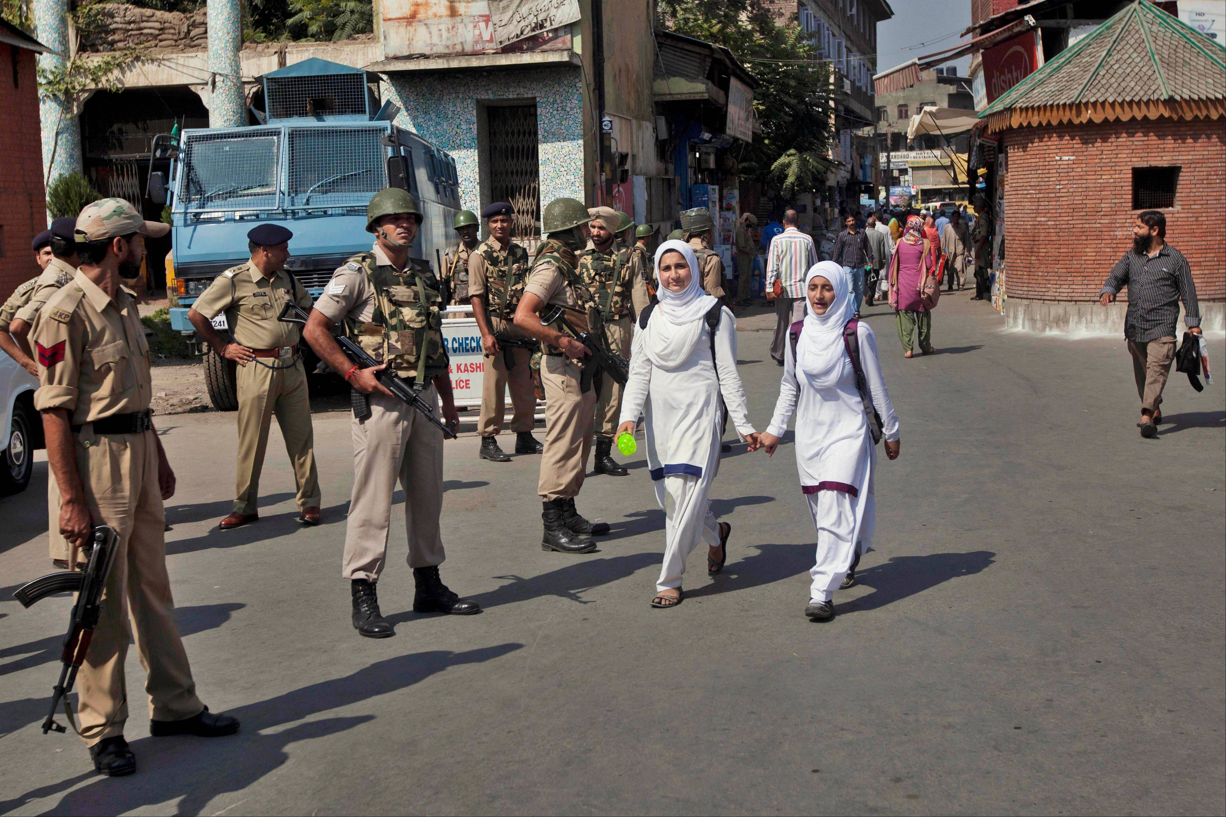 Associated PressKashmiri schoolchildren walk past Indian paramilitary soldiers as they stand guard in Srinagar, India, Saturday, Oct. 5. The Indian army said Saturday that it killed seven suspected rebels in two separate gun battles near the heavily militarized line dividing the disputed Kashmir region between India and Pakistan.