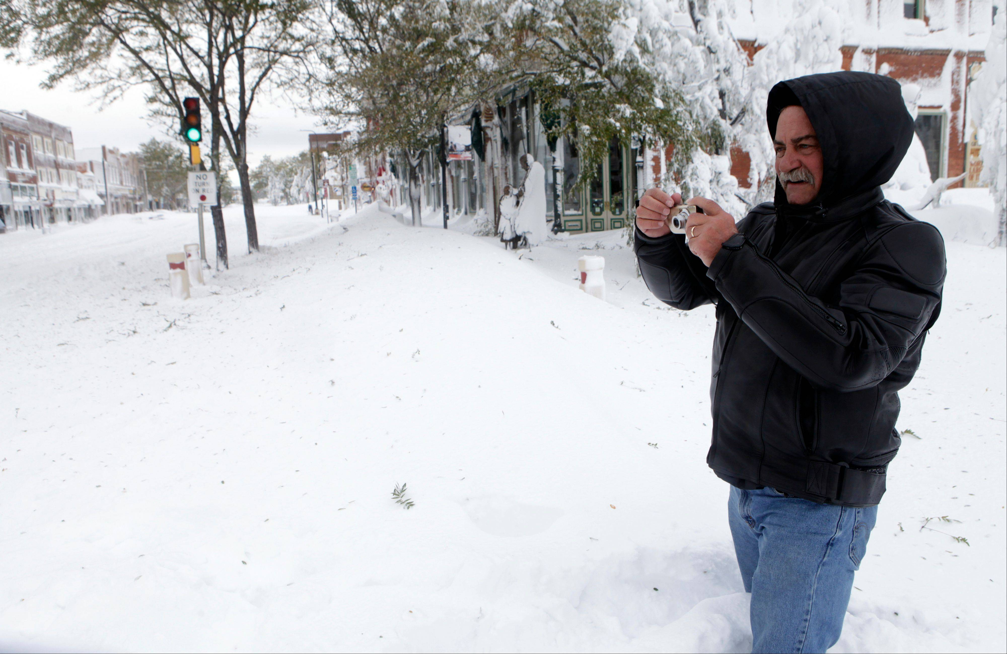 Mike Vonner stands in a snowdrift while taking photos of the blizzard in downtown Rapid City, S.D., Saturday. South Dakota emergency agencies are asking snowmobile operators in the Rapid City area to help find motorists stranded by an autumn storm.